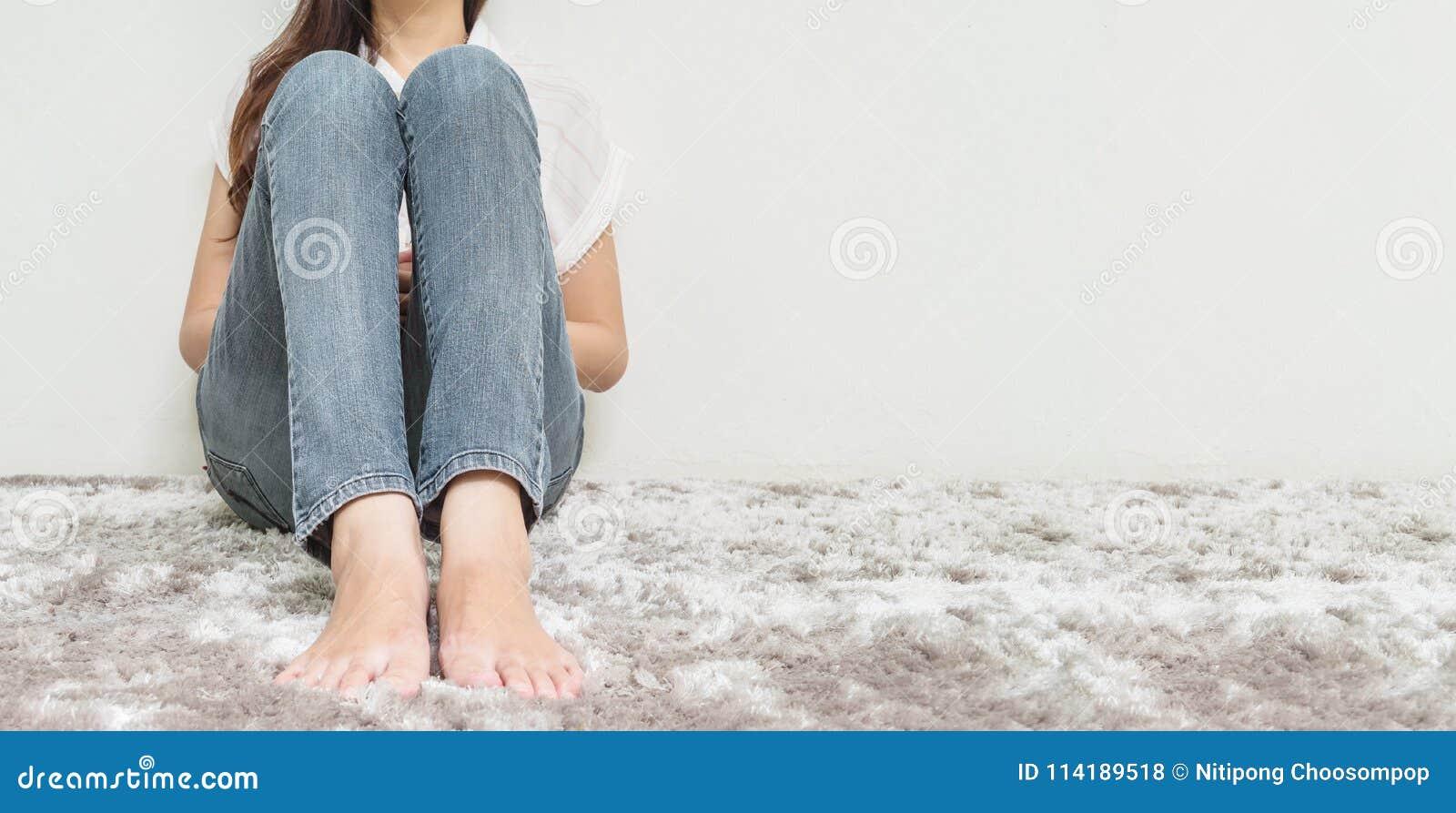 A mulher asiática senta-se no assoalho de tapete cinzento com fundo textured do cimento branco no canto da casa com espaço da cóp