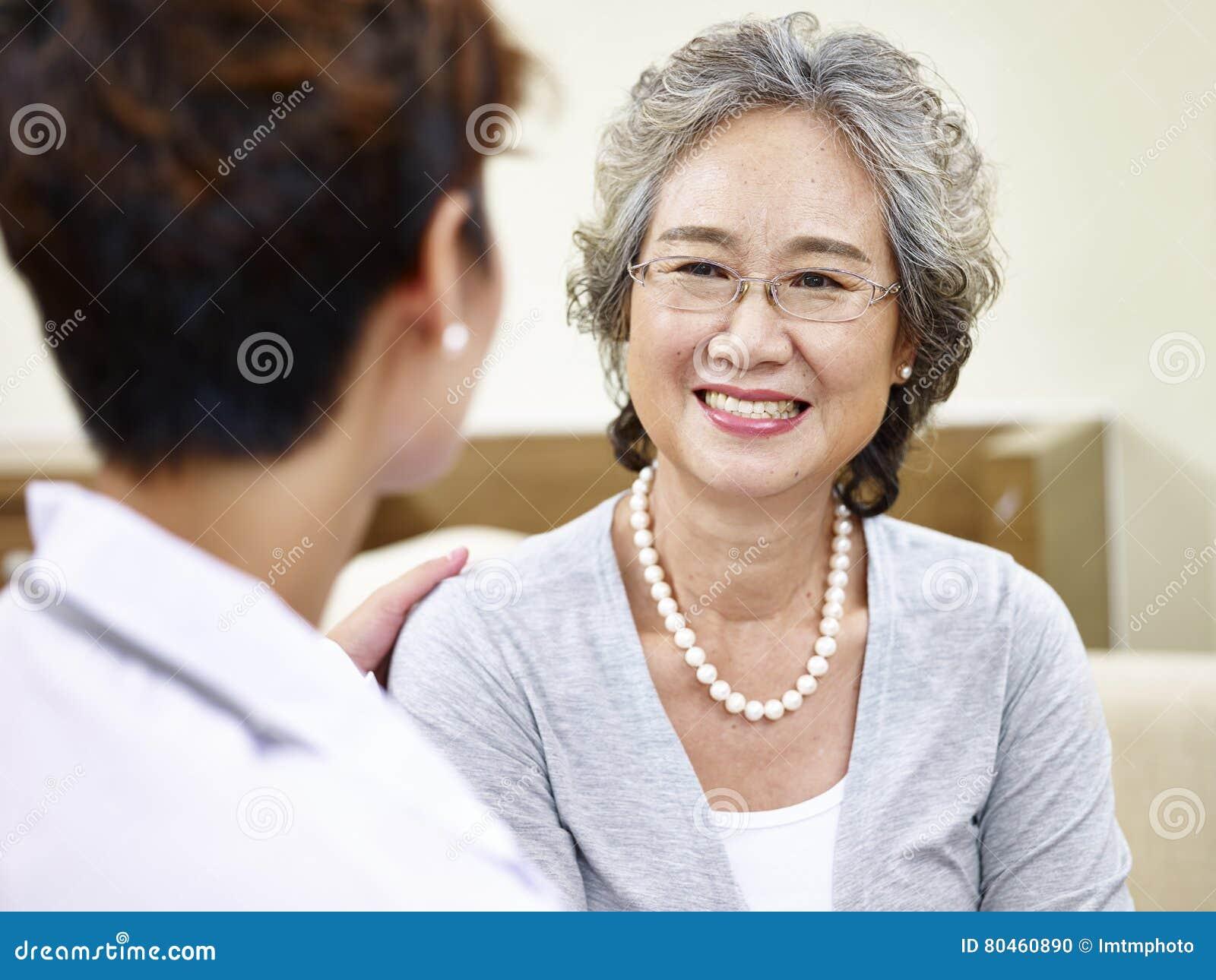 Mulher asiática superior que fala ao médico de família
