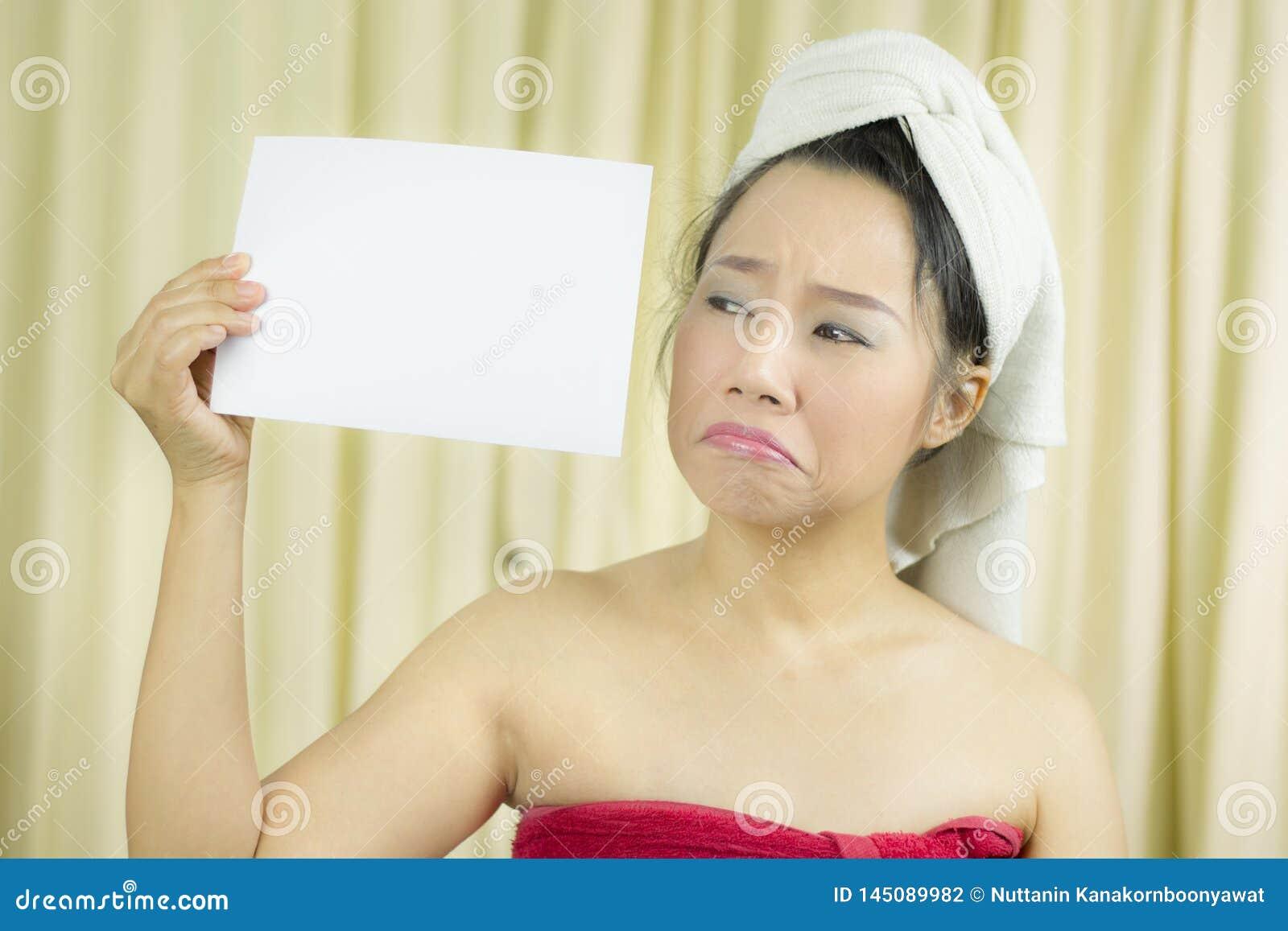 A mulher asi?tica veste uma saia para cobrir seu peito ap?s o cabelo da lavagem, envolvido nas toalhas ap?s o chuveiro que guarda