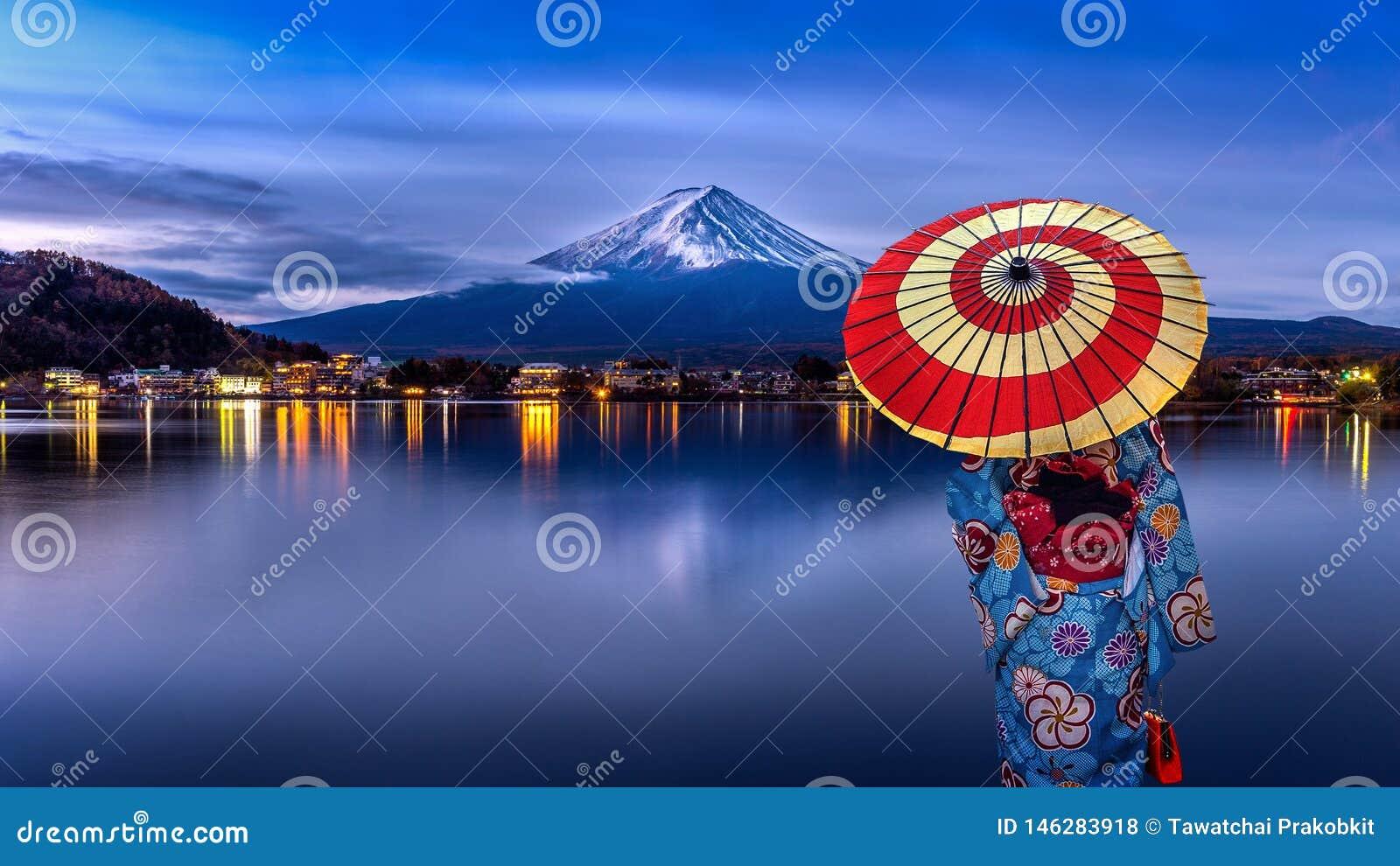 Mulher asi?tica que veste o quimono tradicional japon?s na montanha de Fuji, lago Kawaguchiko em Jap?o