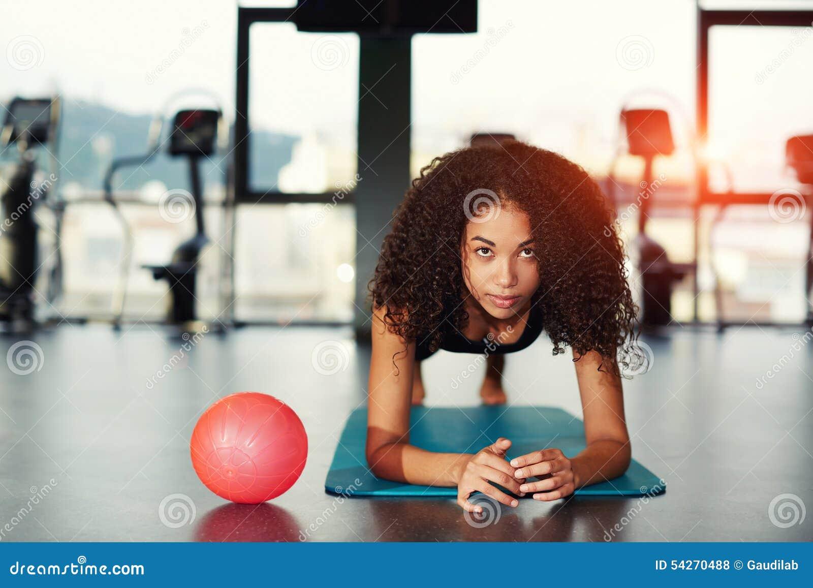 Mulher atrativa com o cabelo encaracolado que inclina-se em seus cotovelos que dão certo no gym