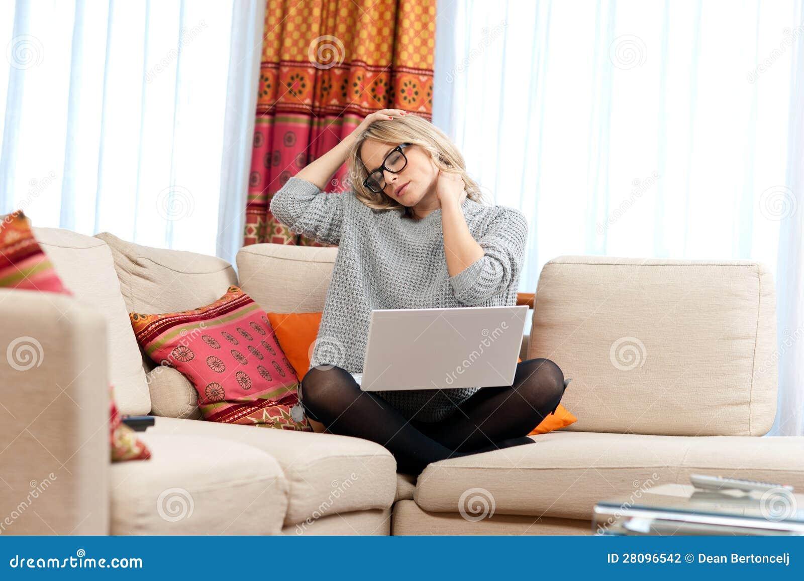 Mulher atrativa com o portátil que tem a dor de pescoço