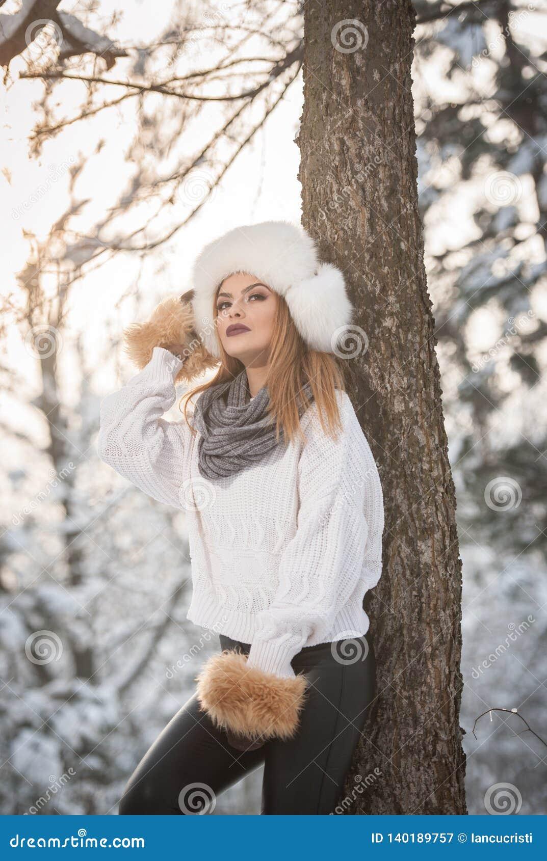 Mulher atrativa com o tampão e o revestimento brancos da pele que aprecia o inverno Ideia lateral do levantamento louro elegante