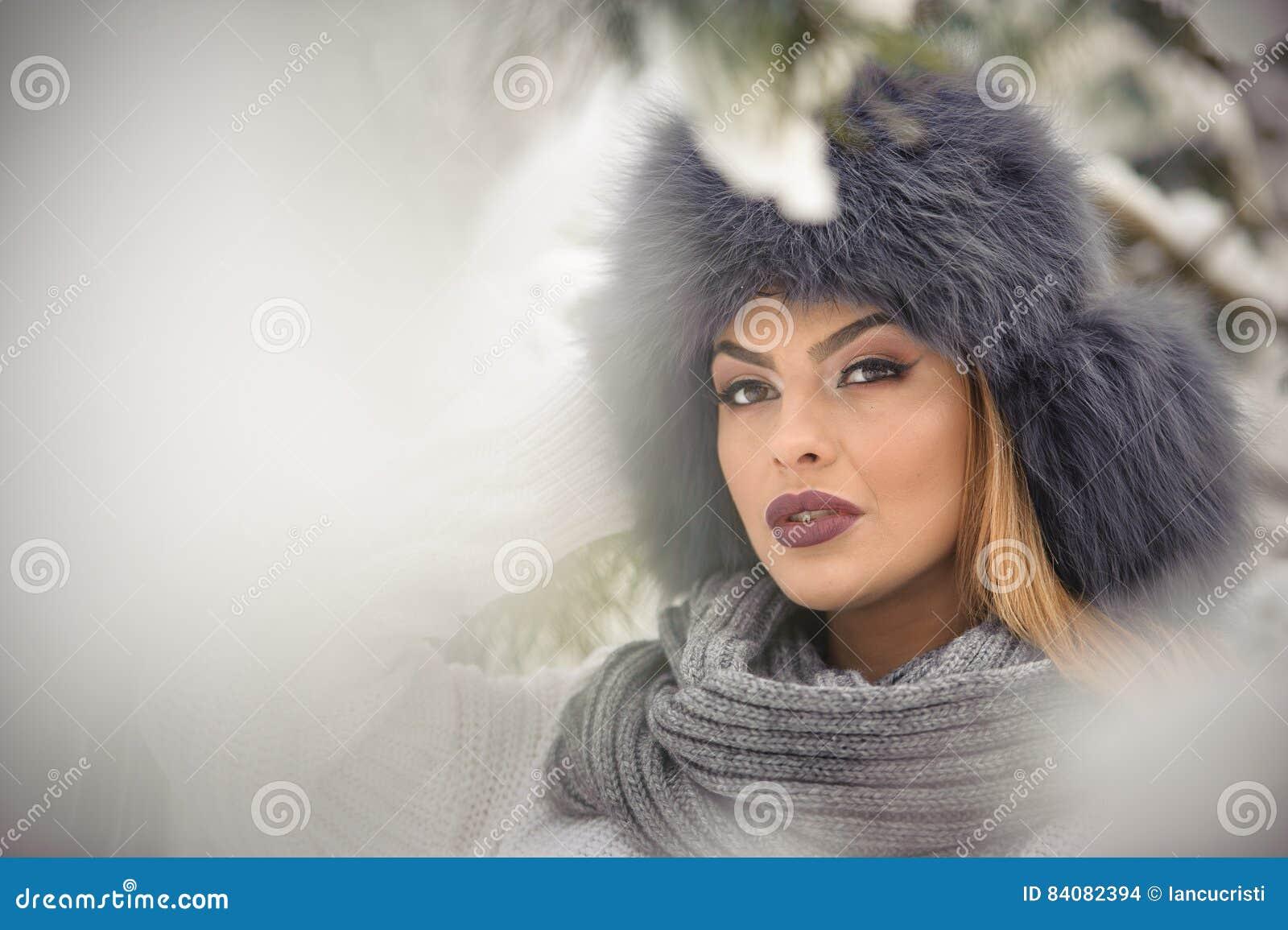 Mulher atrativa com o tampão preto da pele e o xaile cinzento que aprecia o inverno Opinião frontal a menina moreno elegante com