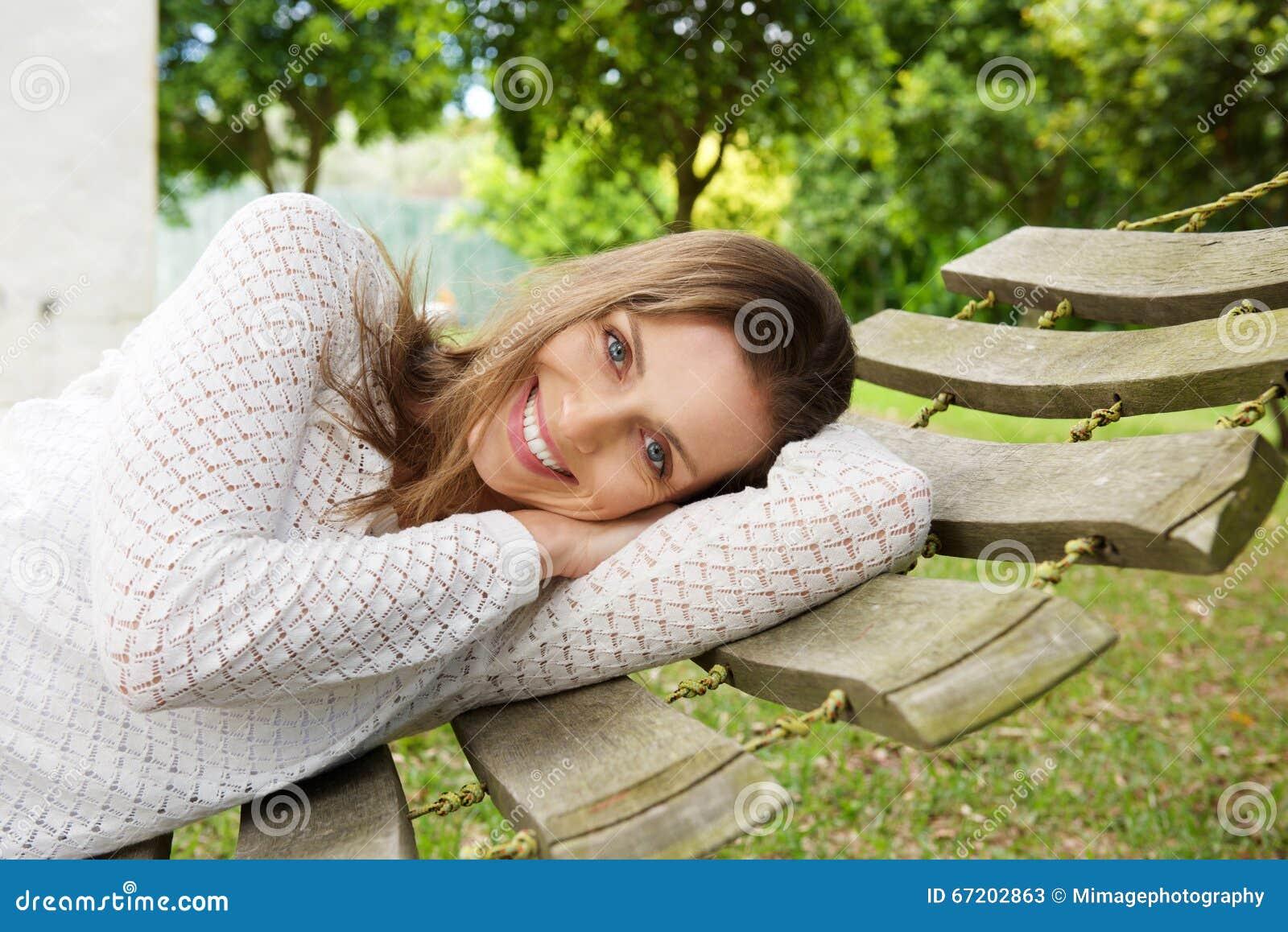 Mulher atrativa de sorriso que relaxa na rede fora