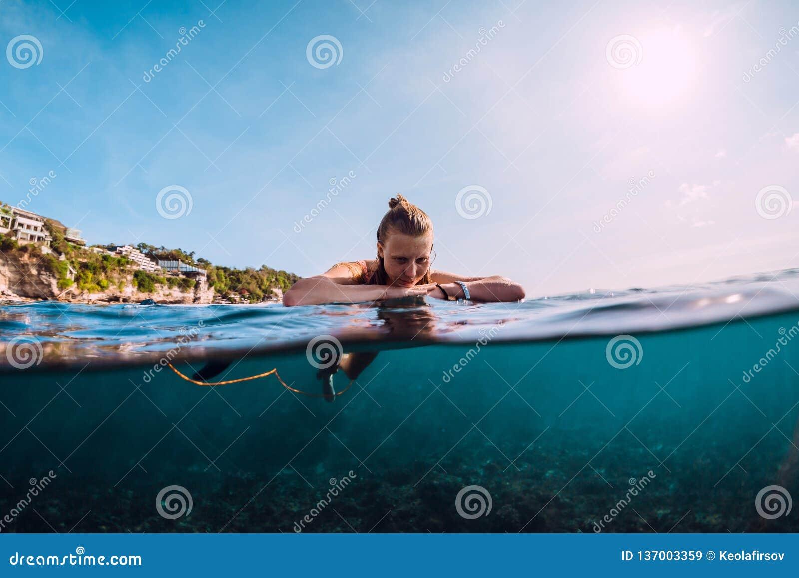 A mulher atrativa do surfista relaxa no mar