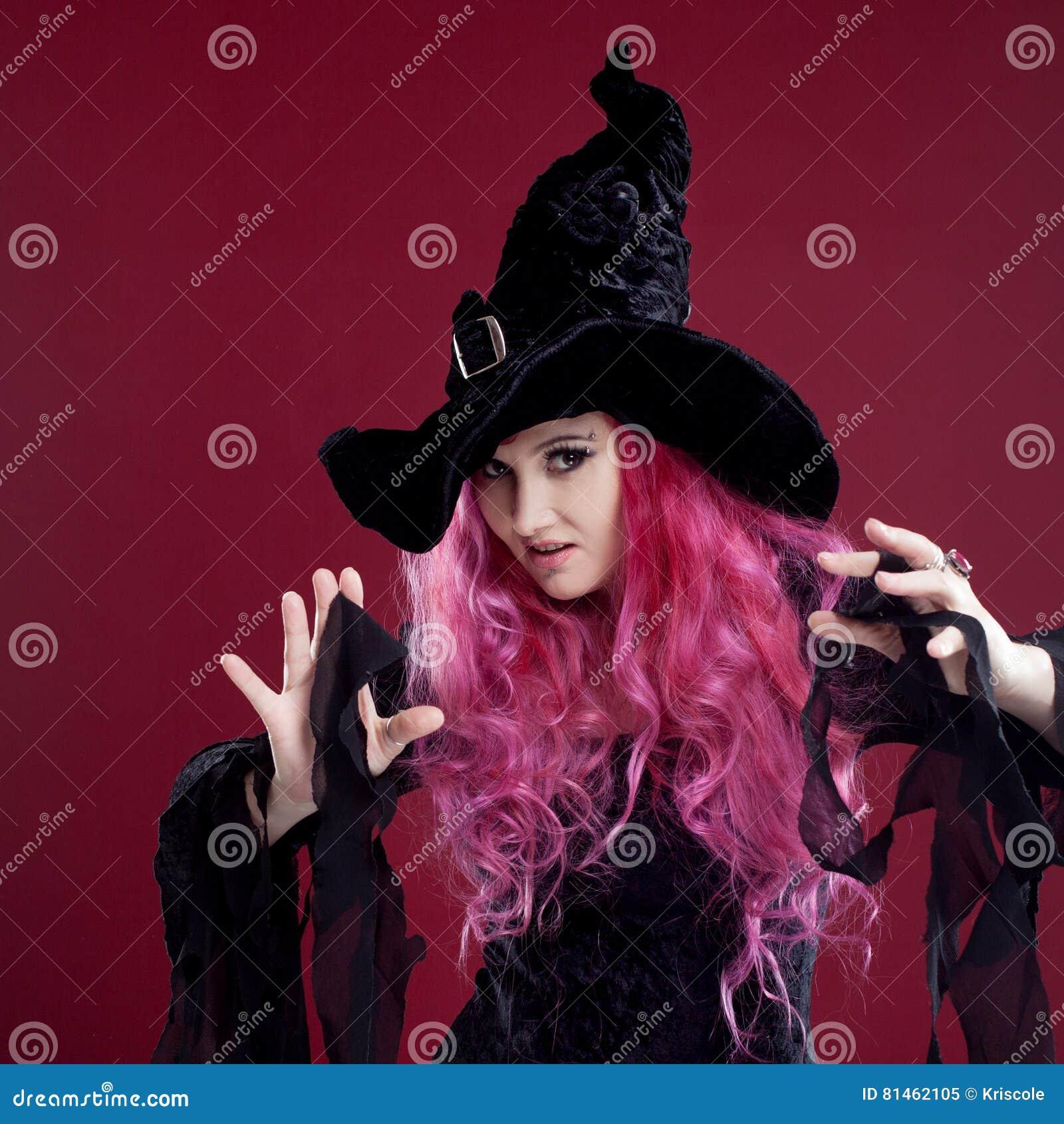 A mulher atrativa nas bruxas chapéu e traje com cabelo vermelho executa a  mágica em um fundo cor-de-rosa Dia das Bruxas 76077292a6f