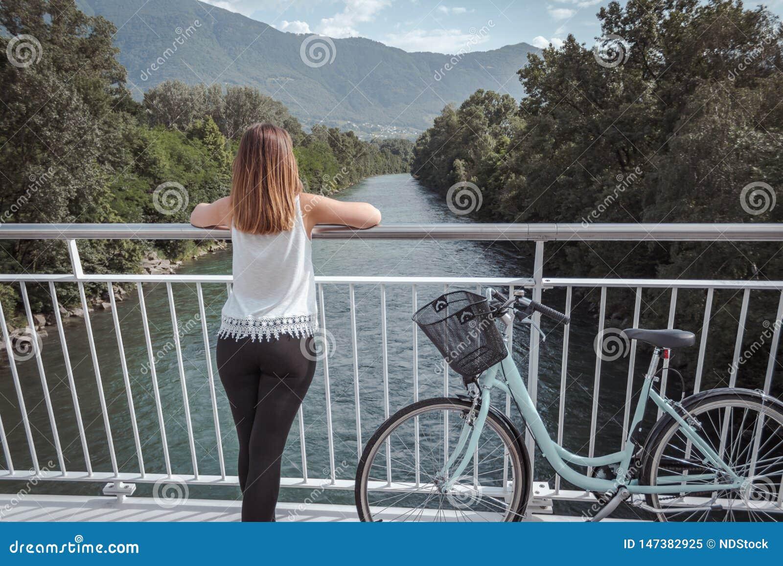 Mulher atrativa nova com bicicleta em uma ponte