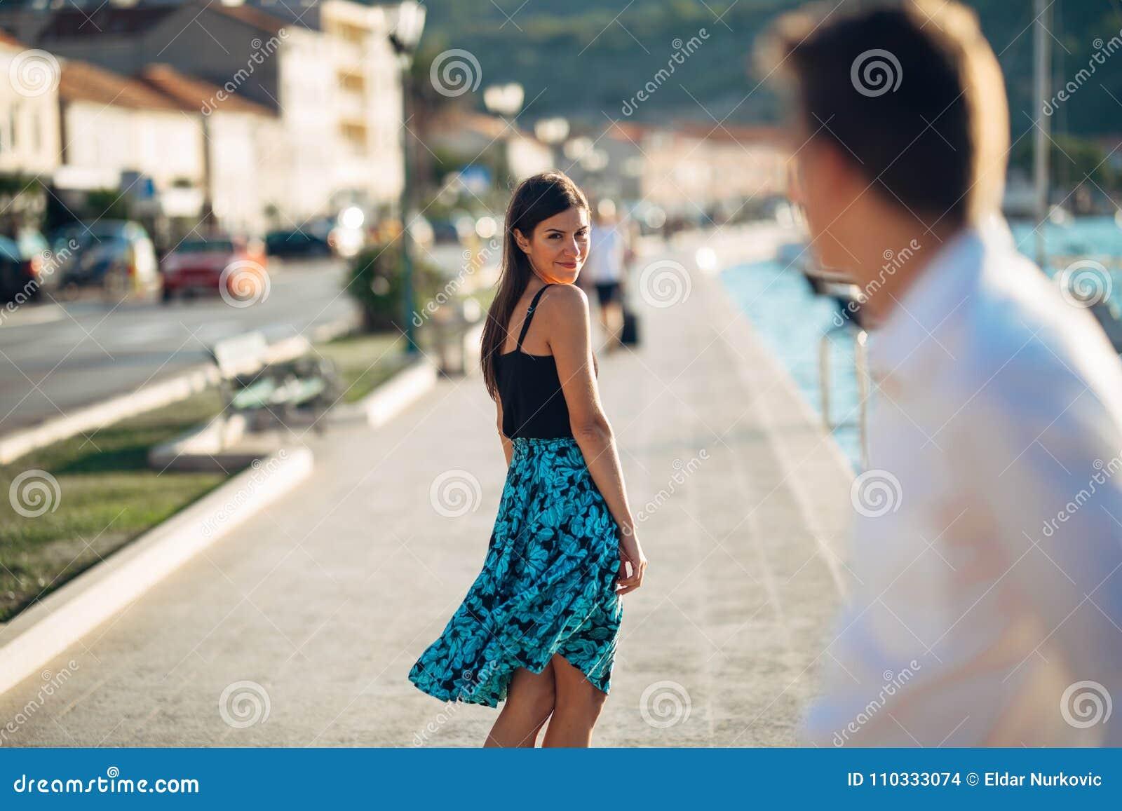 Mulher atrativa nova que flerta com um homem na rua Mulher de sorriso Flirty que olha para trás em um homem considerável Atração