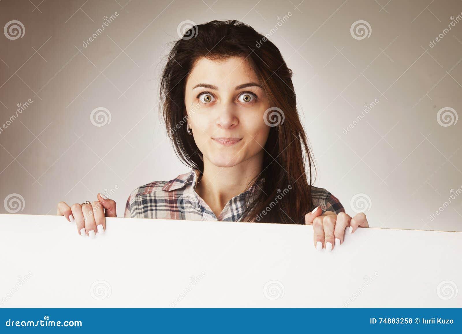 Mulher atrativa que espreita atrás de um whiteboard