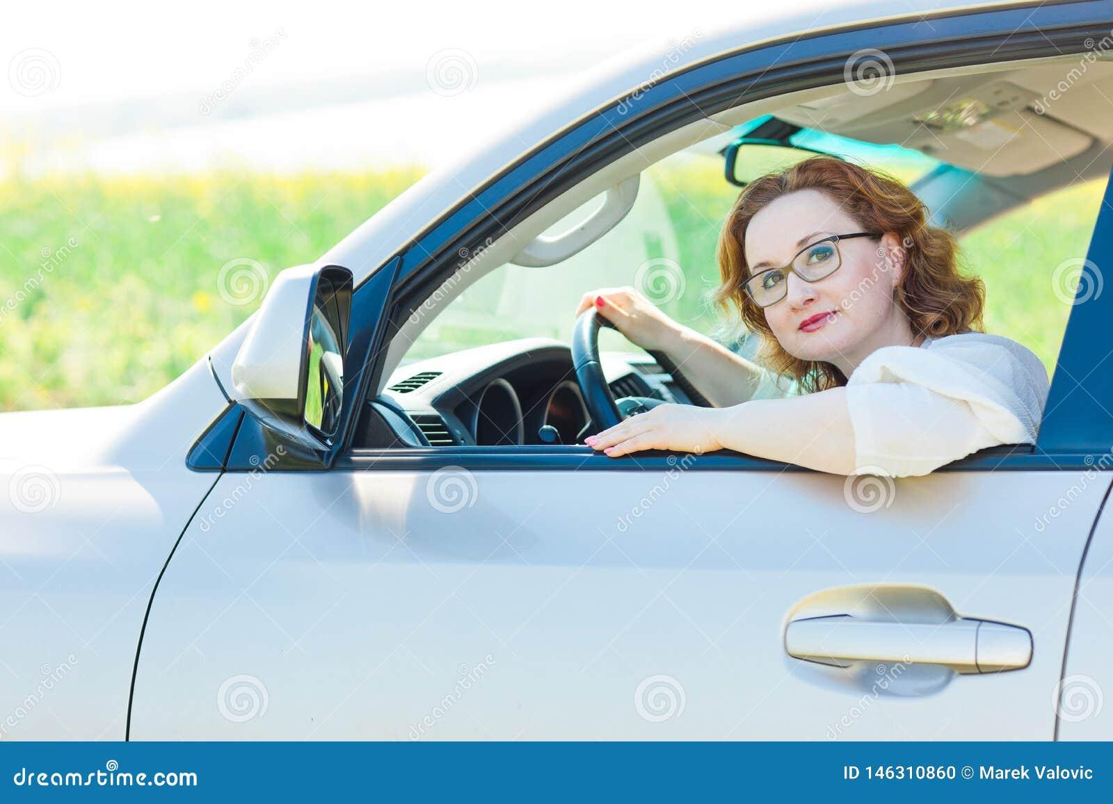 Mulher atrativa que levanta no carro no assento de motoristas