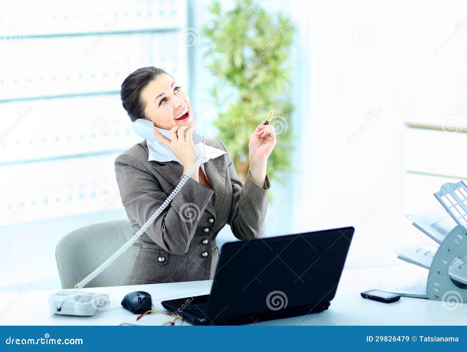 Mulher atrativa que senta-se na mesa no trabalho no telefonema da linha terrestre,