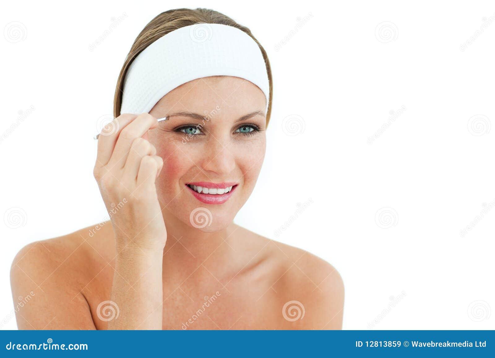 Mulher atrativa que usa tweezers