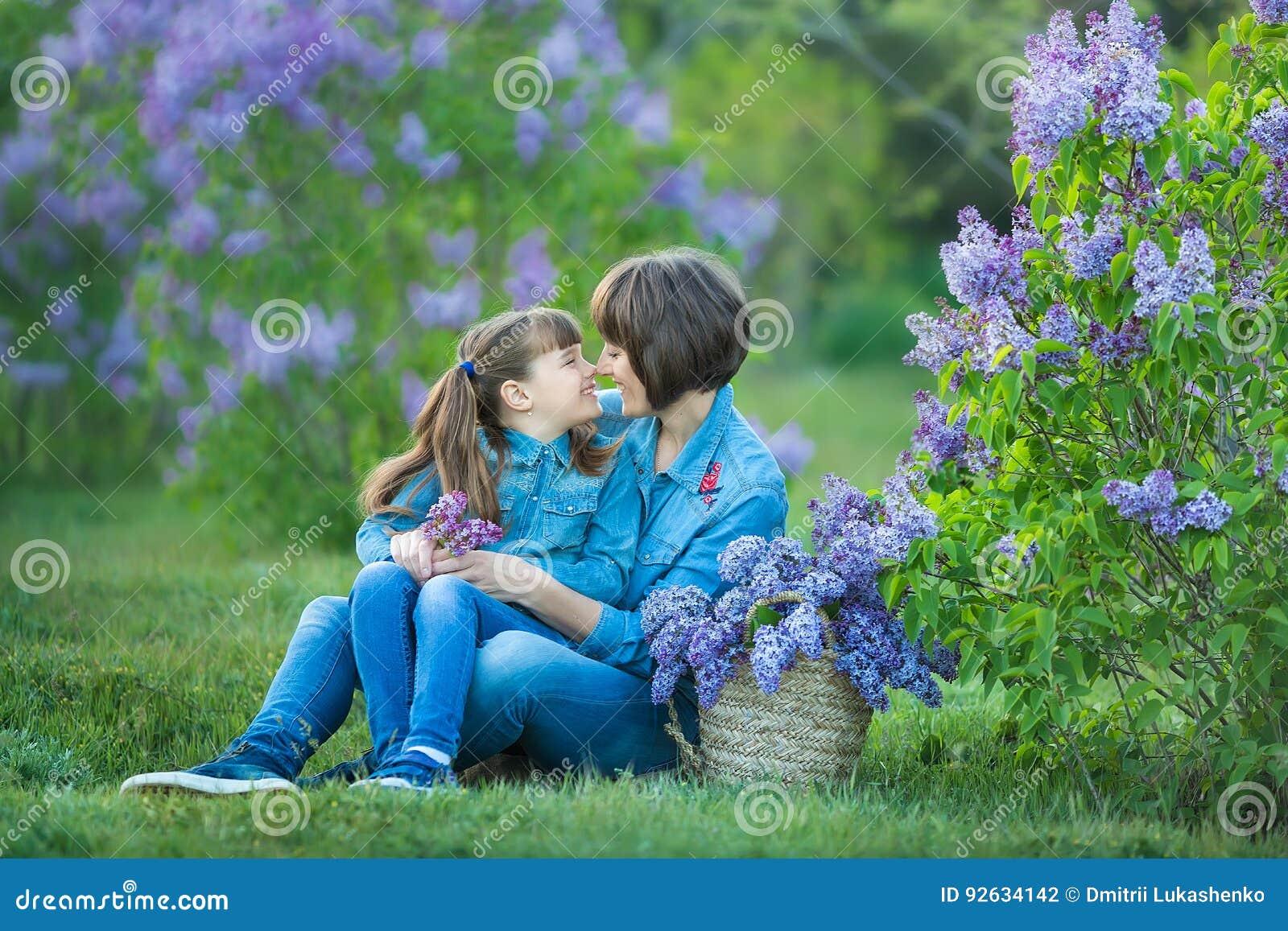 Mulher bonita adorável bonito da mamã da senhora da mãe com a filha moreno da menina no prado do arbusto roxo lilás Povos no desg