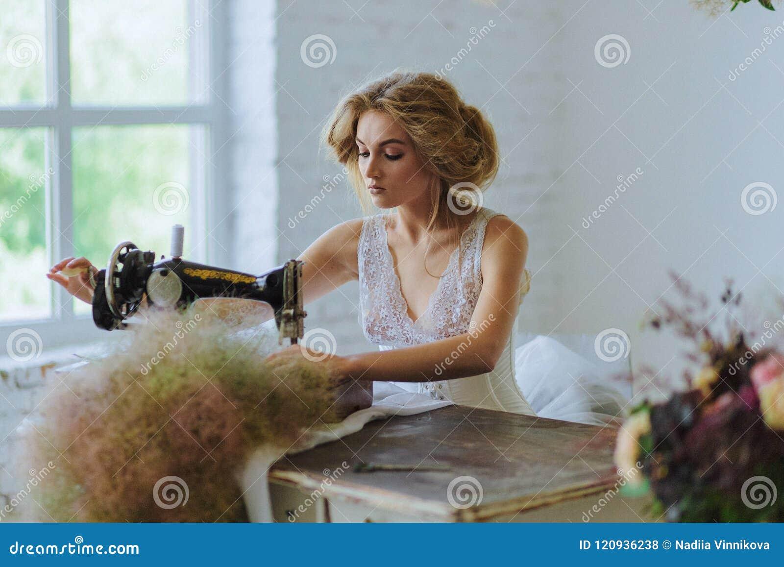 Mulher bonita Ao estilo de Coco Chanel que senta-se em uma máquina de costura
