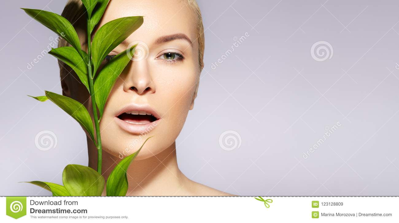 A mulher bonita aplica o cosmético orgânico Termas e wellness Modele com pele limpa, composição natural, folha Copie o espaço