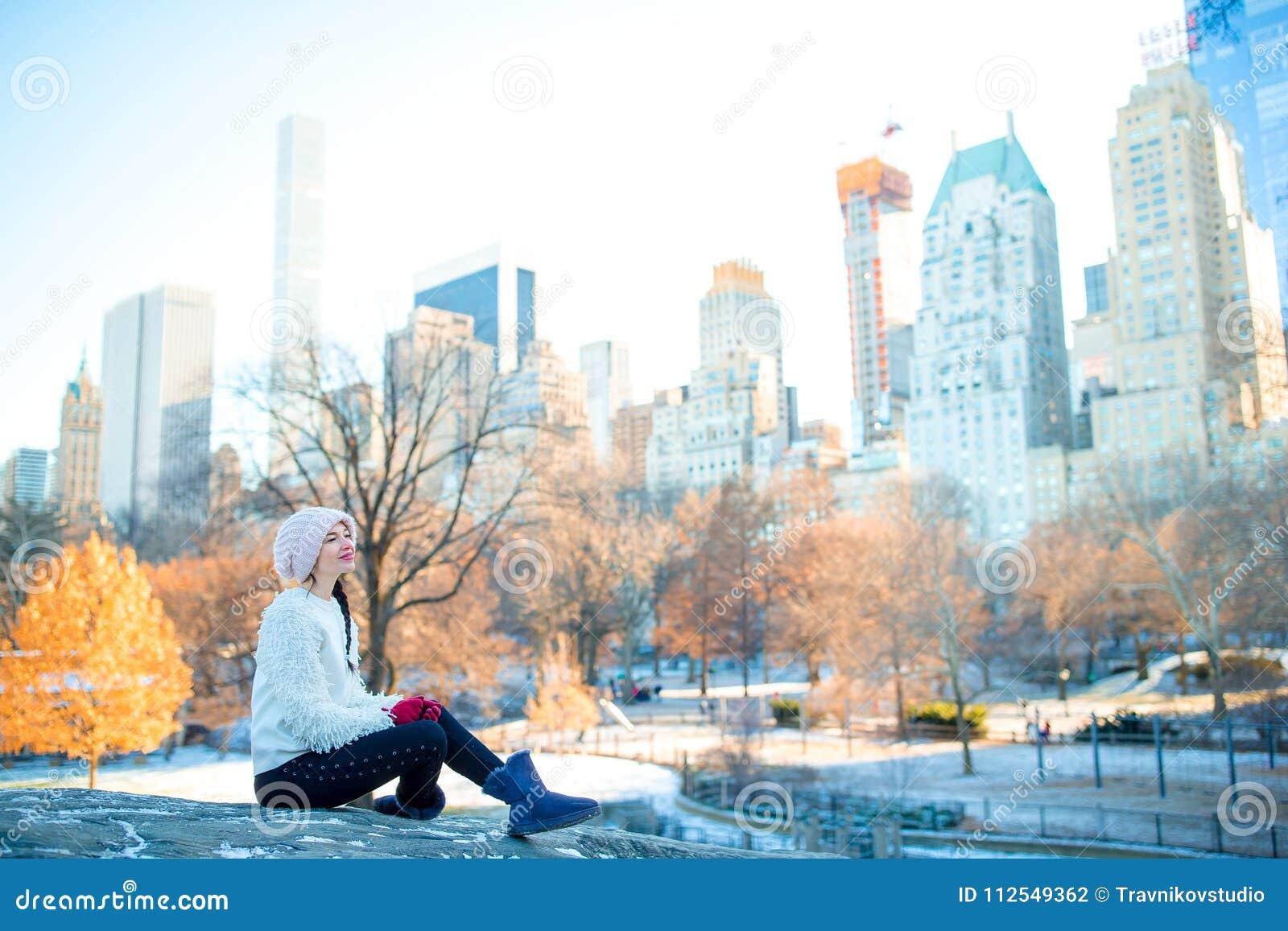 A mulher bonita aprecia a vista da gelo-pista no Central Park e nos arranha-céus em Manhattan em New York City