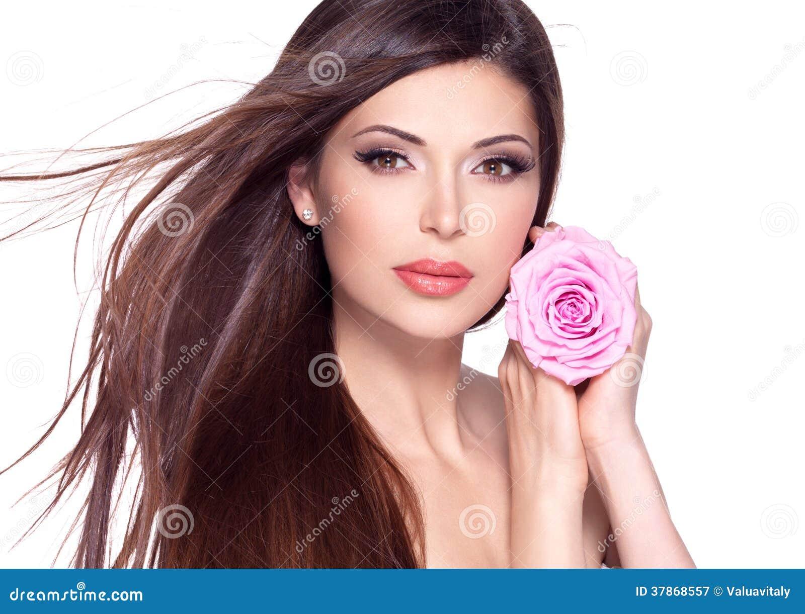 Mulher bonita bonita com a rosa longa do cabelo e do rosa na cara.