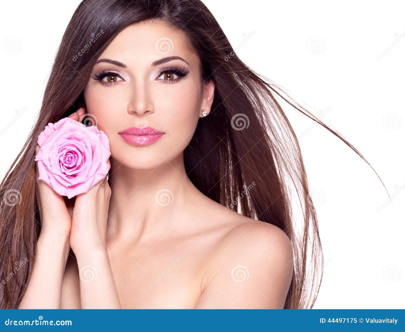Mulher bonita bonita com a rosa longa do cabelo e do rosa na cara