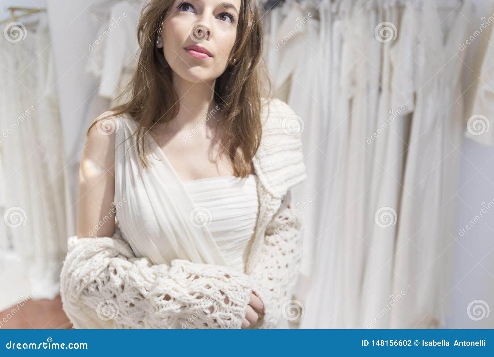 A mulher bonita cabe em um vestido branco no shopping em uma oficina