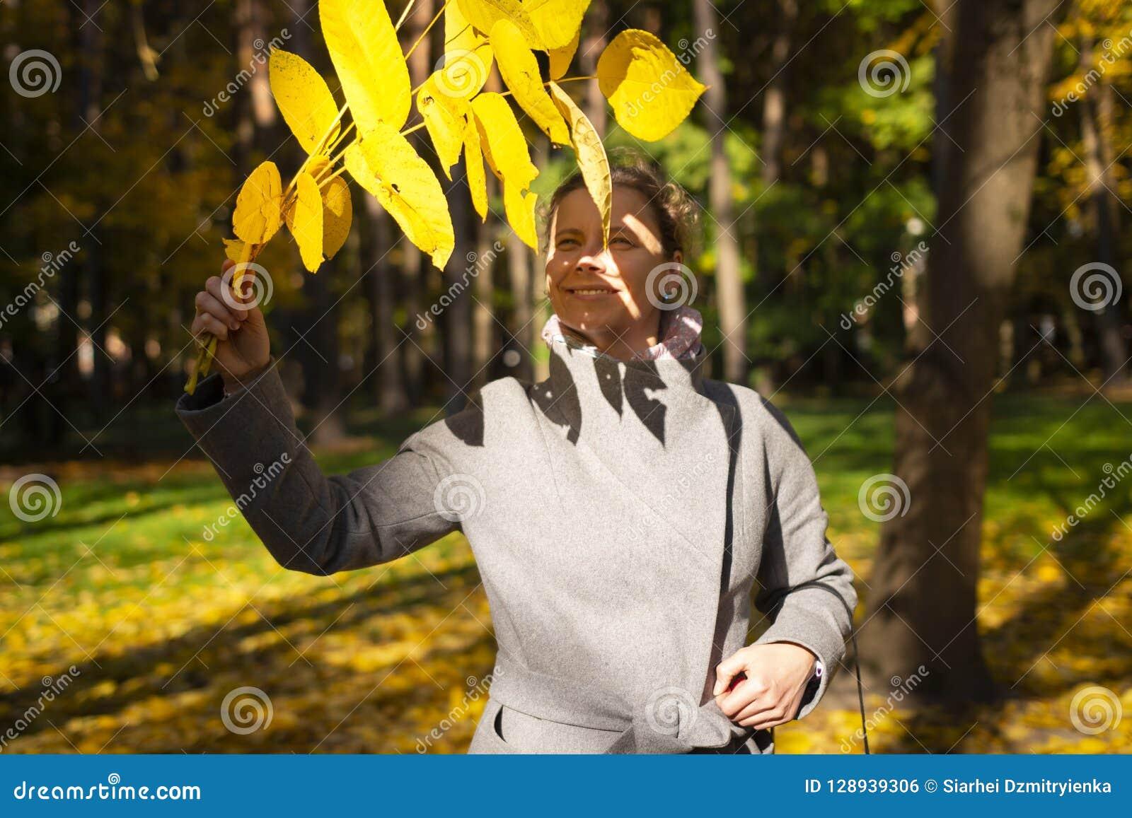 A mulher bonita com amarelo sae à disposição no parque colorido do outono no dia ensolarado Modo outonal A menina feliz anda em P