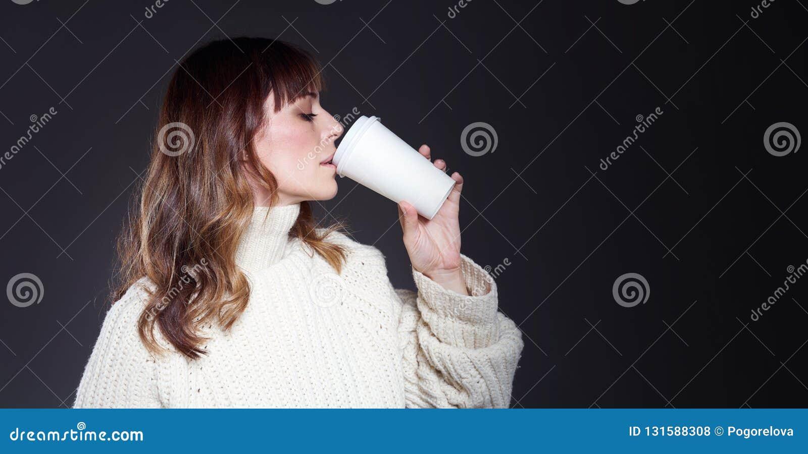 A mulher bonita com a camiseta vestindo do cabelo longo guarda o copo de café descartável de papel Café bebendo com a cara relaxa