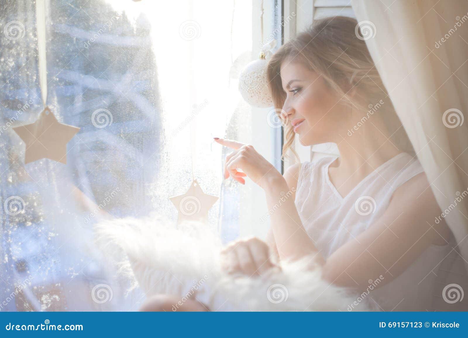A mulher bonita com composição diária fresca e o penteado ondulado romântico, sentando-se na soleira, tira no vidro