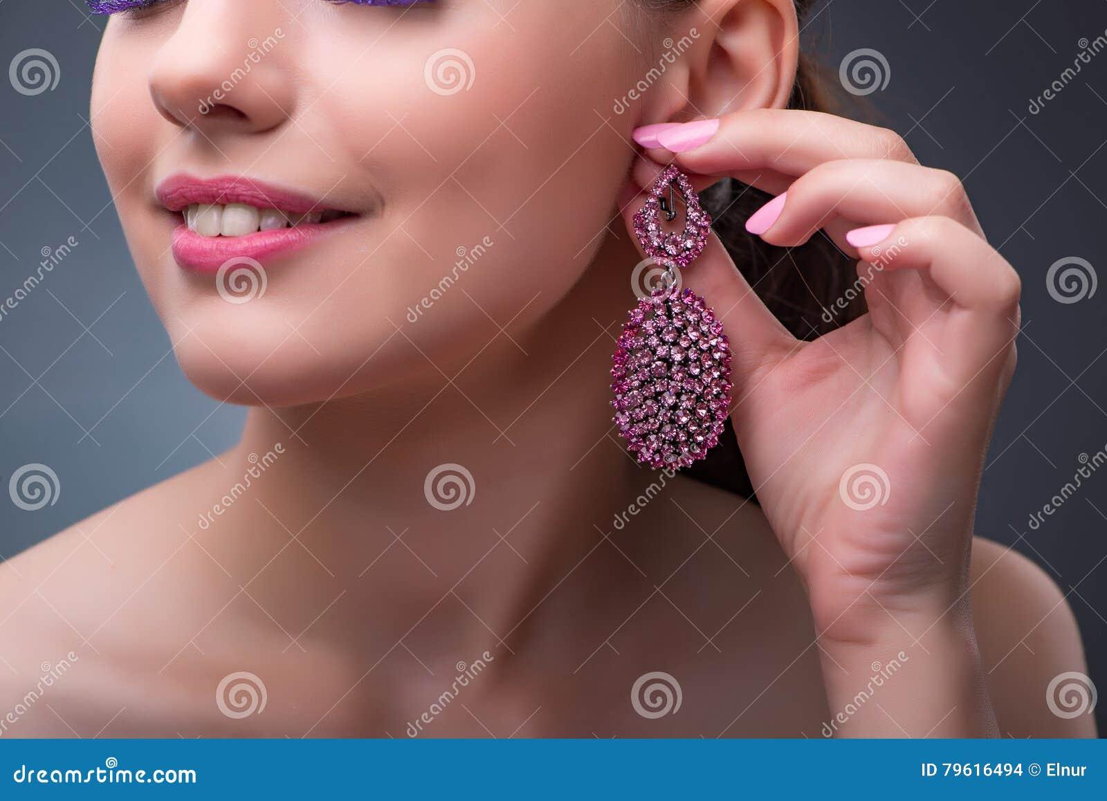 A mulher bonita com joia no conceito da forma