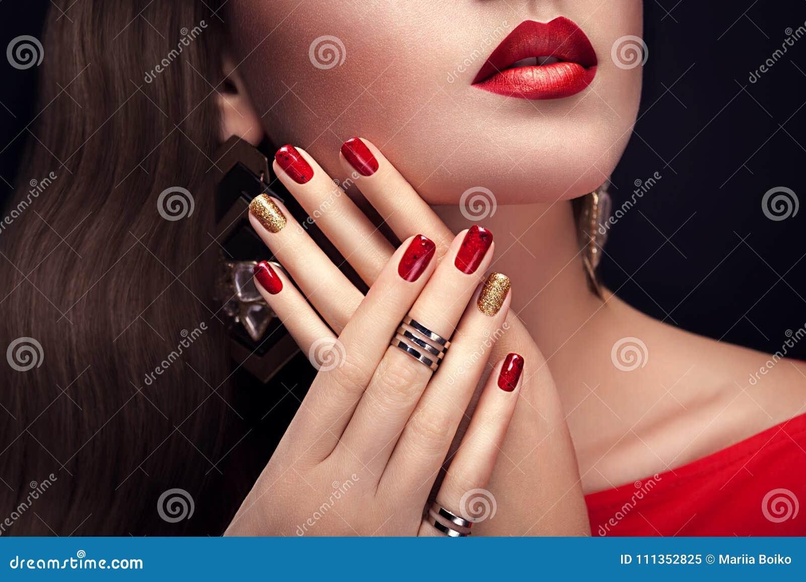Mulher bonita com joia vestindo da composição perfeita e do tratamento de mãos vermelho e dourado