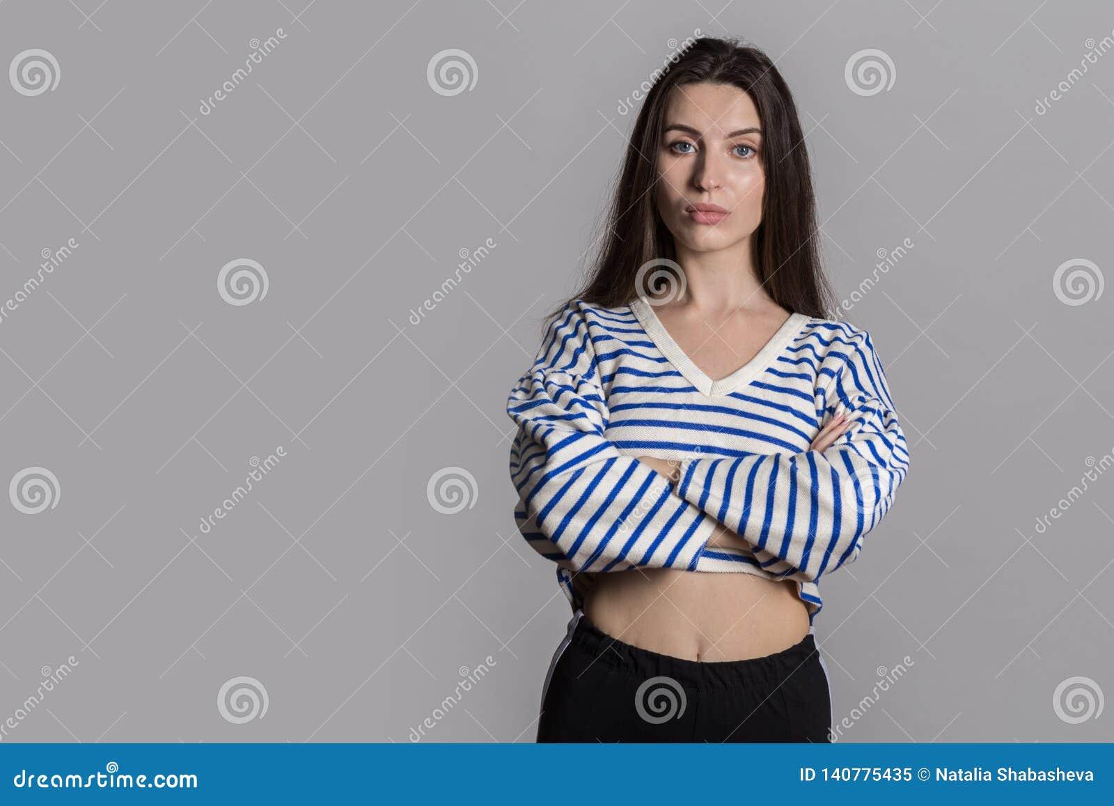 Mulher bonita com o cabelo macio, vestido ocasionalmente contra uma parede cinzenta do estúdio