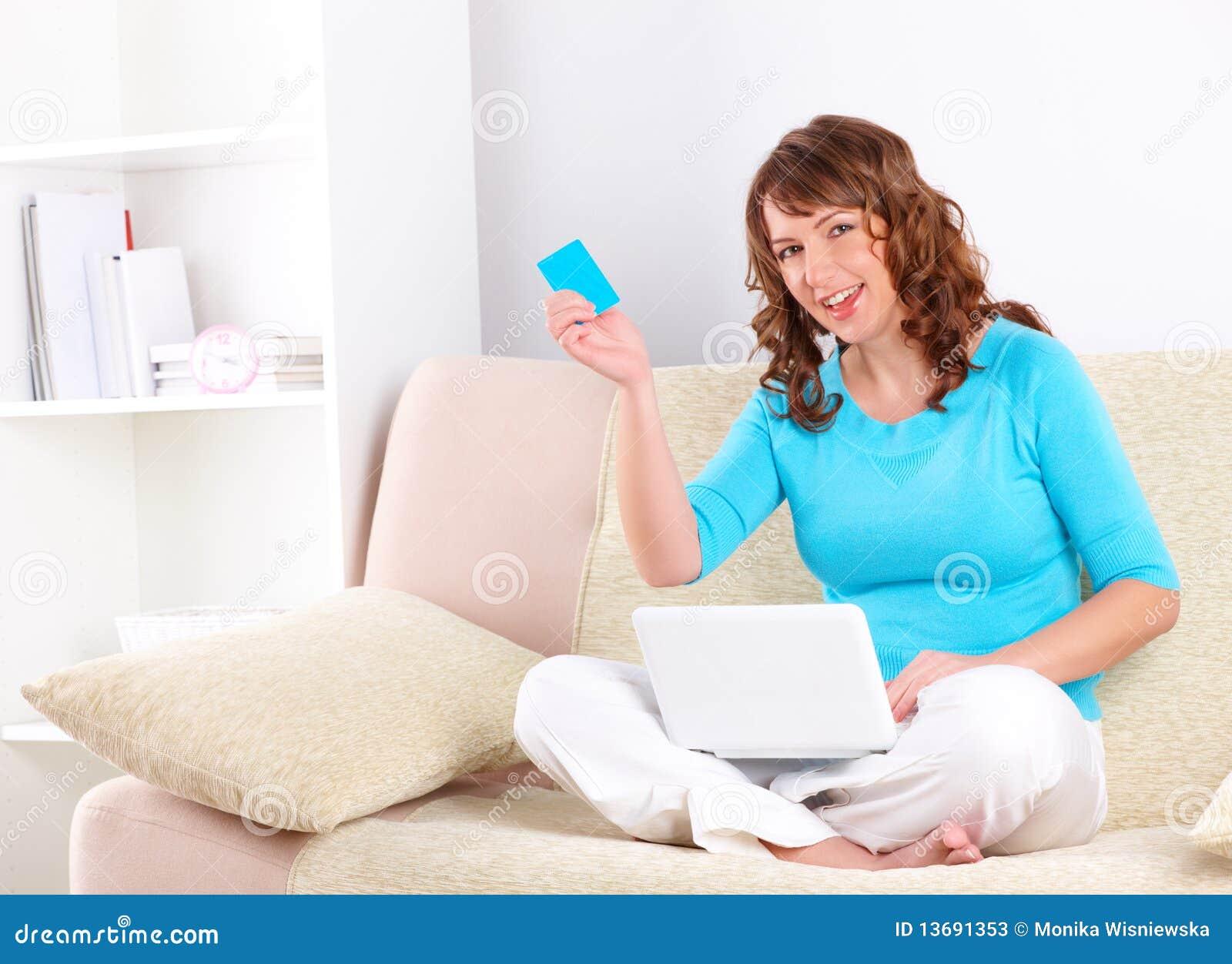 Mulher bonita com o cartão do netbook e de crédito