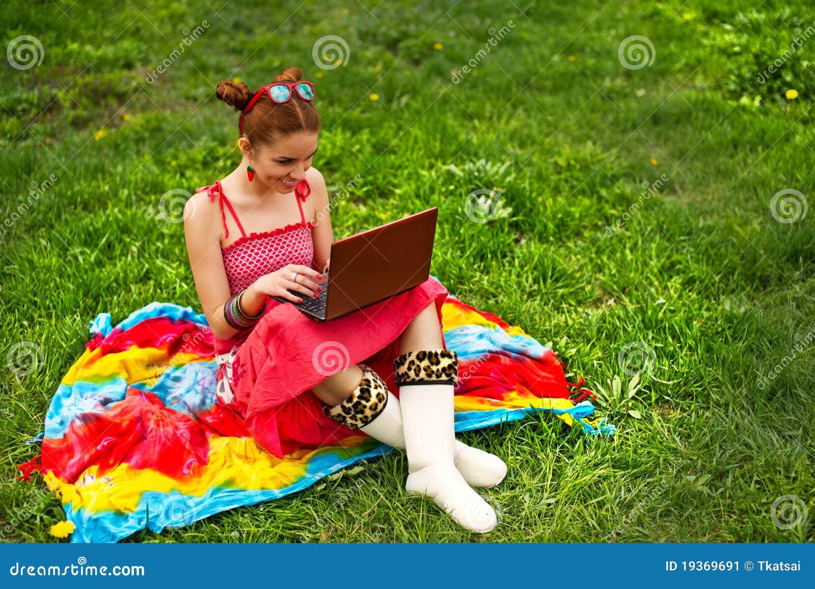 Mulher bonita com o portátil na grama