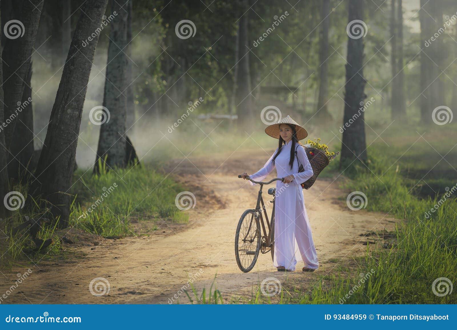 Mulher bonita com o vestido tradicional da cultura de Vietname, traje tradicional, estilo do vintage, Vietname