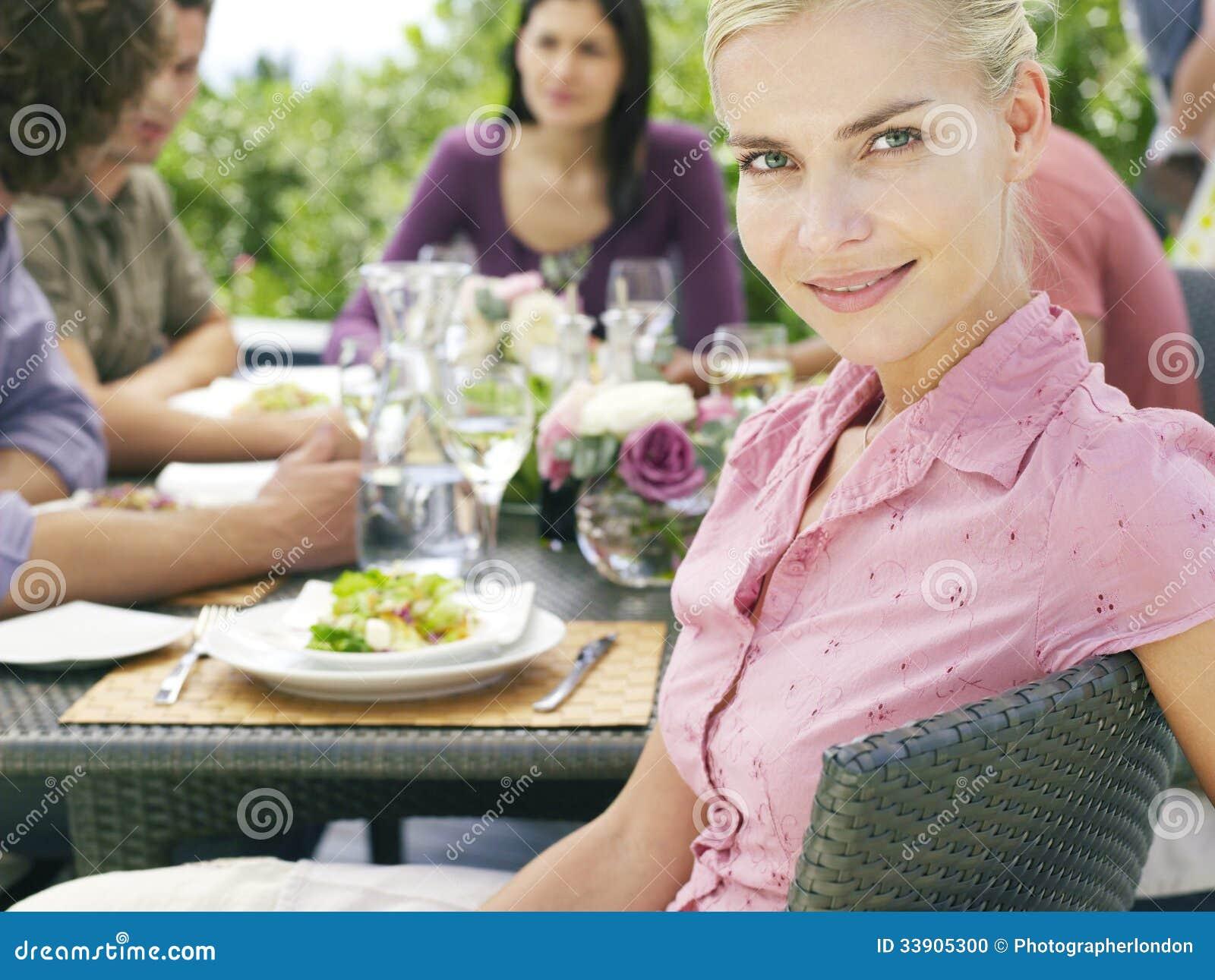 Mulher bonita com os amigos que têm a refeição fora