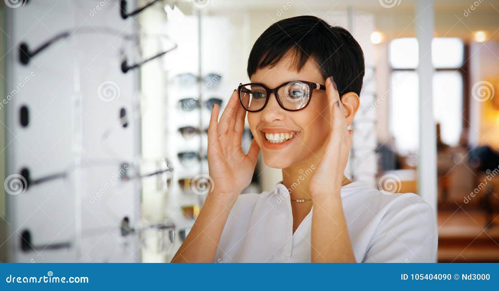 Mulher bonita com os monóculos de tentativa do ótico