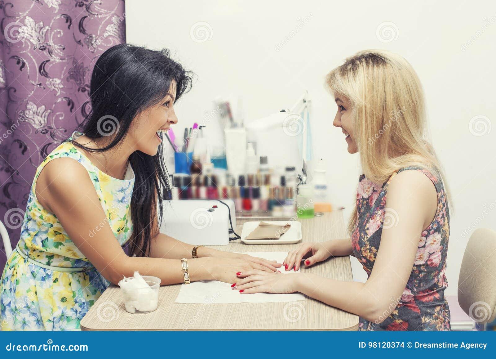 A mulher bonita com salão de beleza o cliente faz o manikpur