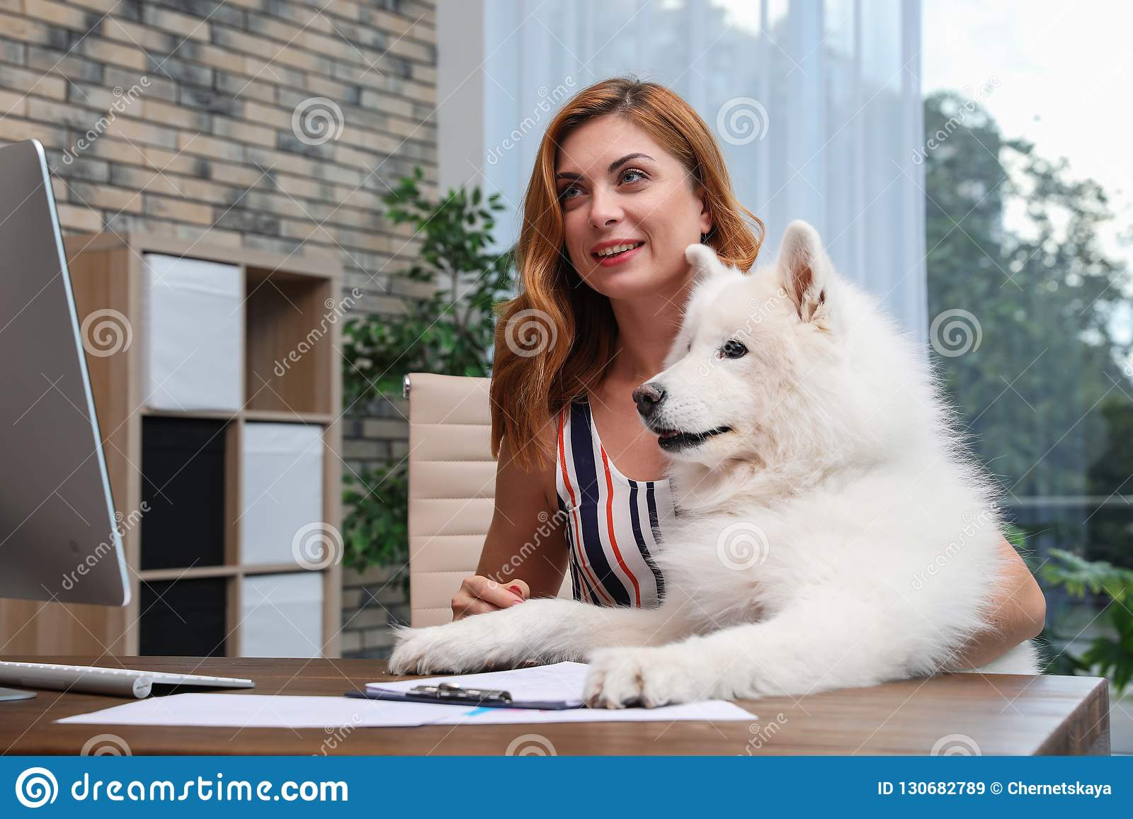 Mulher bonita com seu cão que senta-se na tabela