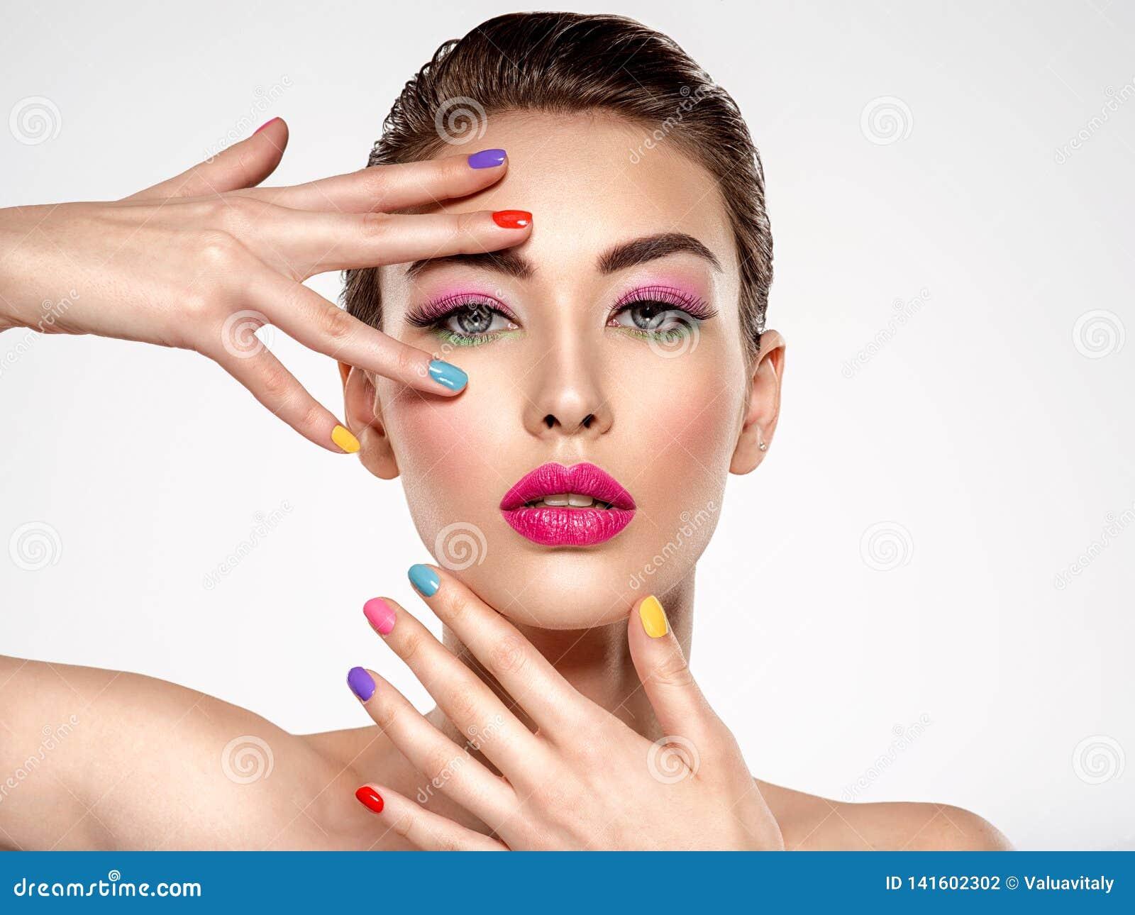 Mulher bonita da forma com pregos coloridos Menina branca atrativa com tratamento de mãos multicolorido