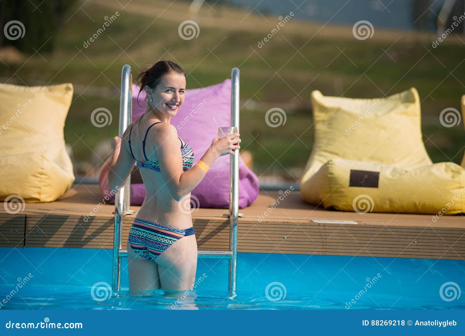 A mulher bonita da vista traseira no roupa de banho é saída da associação, girada ao redor
