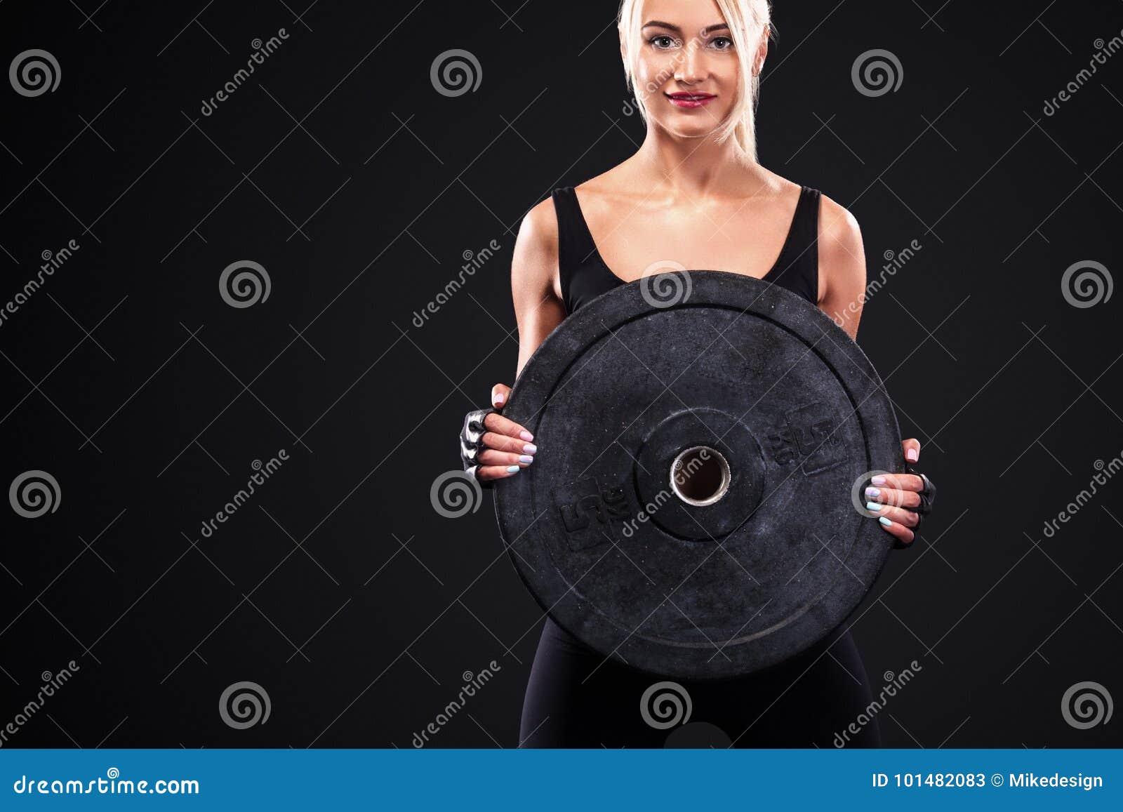 Mulher bonita desportiva que faz o exercício que exercita no fundo preto para ficar apto