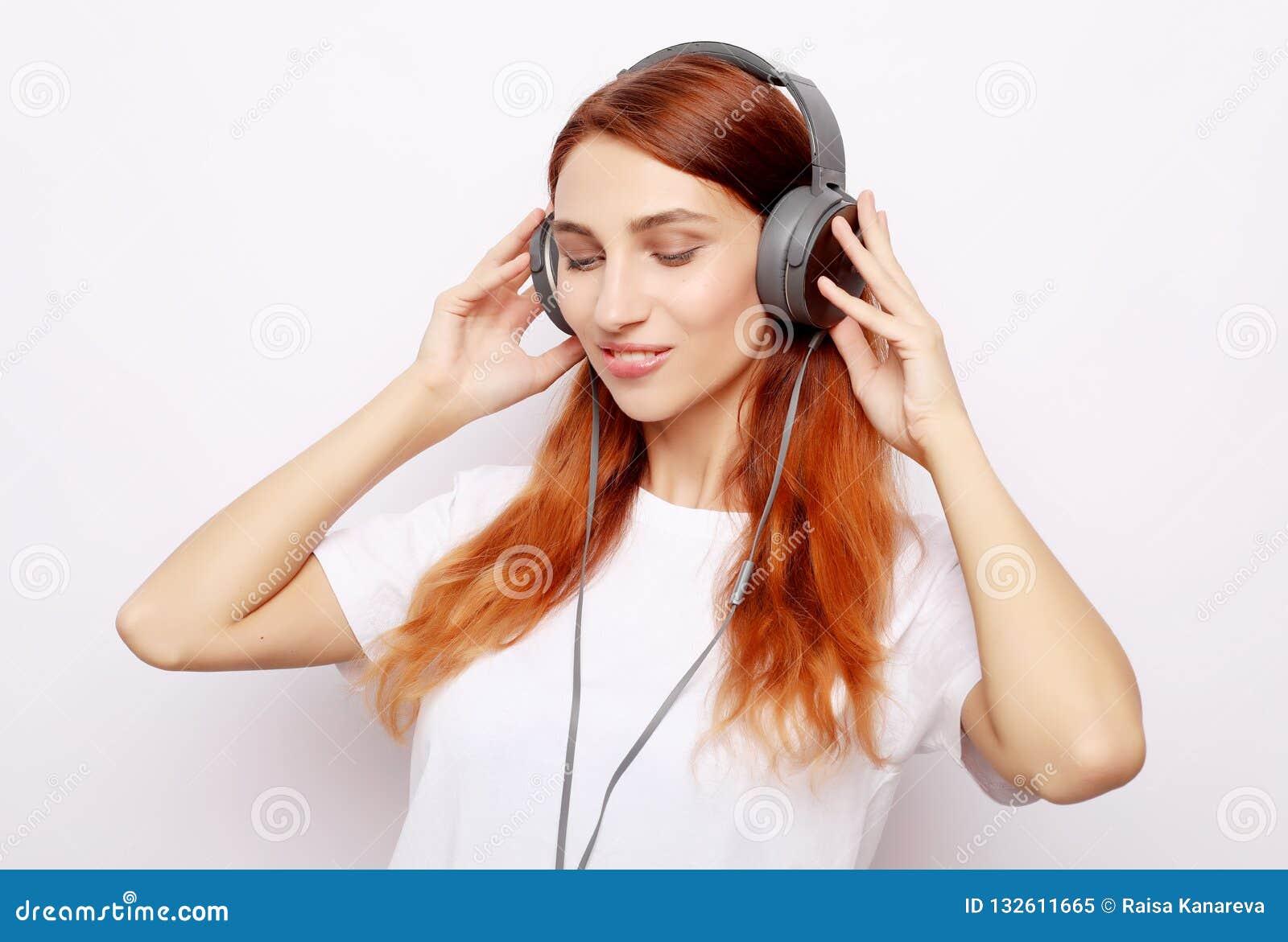 Mulher bonita do redhair nos fones de ouvido que escuta a música