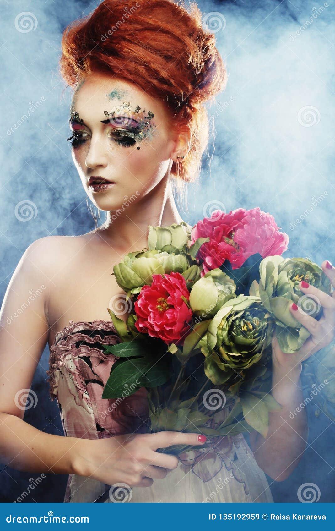 Mulher bonita do redhair que guarda flores