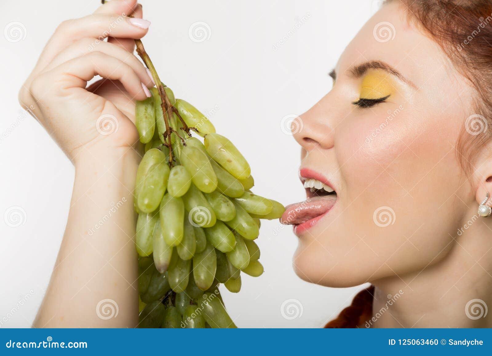 A mulher bonita do ruivo lambe uvas Conceito de comer saudável