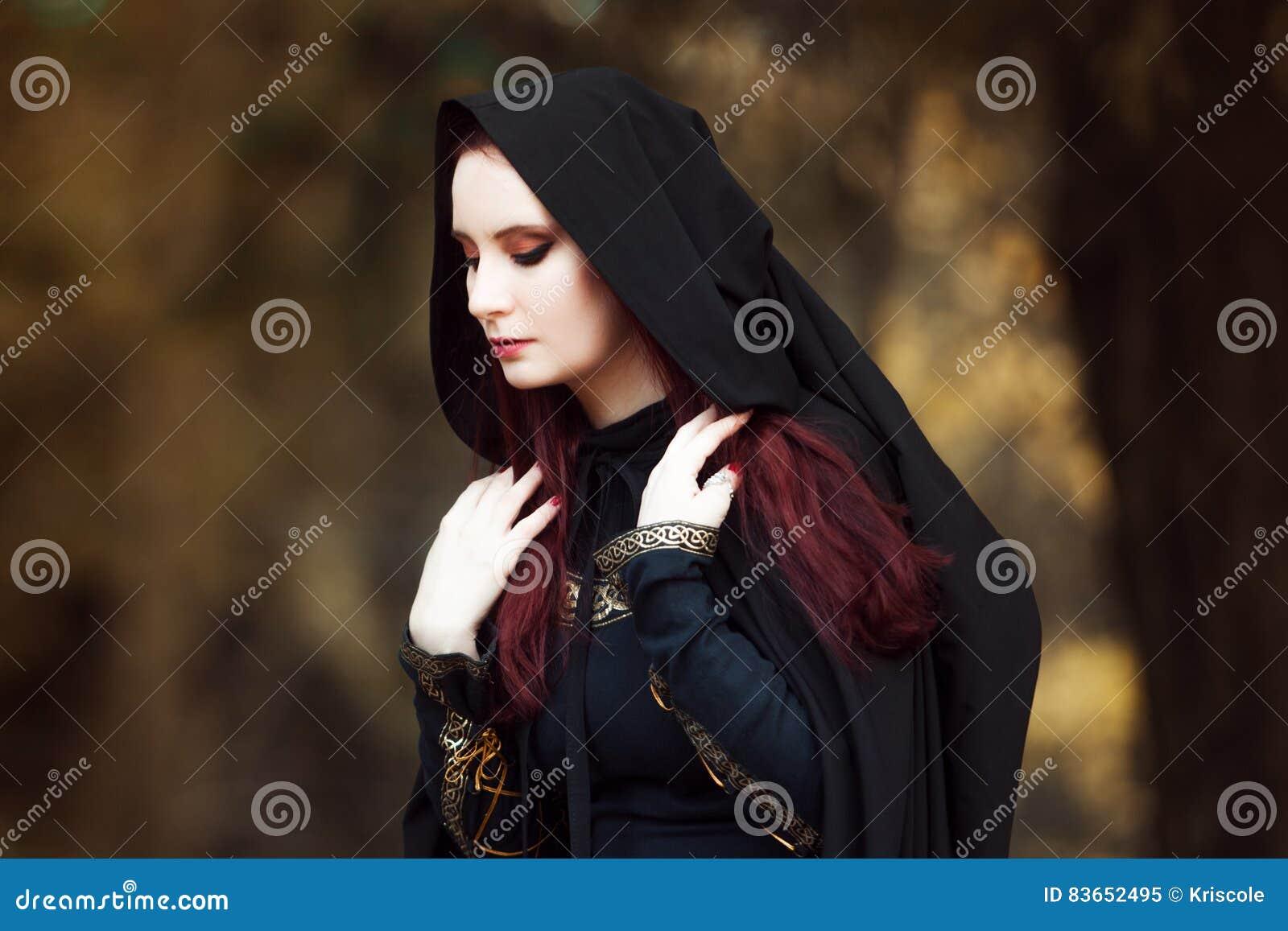 Mulher bonita e misteriosa nova nas madeiras, no casaco preto com capa, na imagem do duende da floresta ou na bruxa