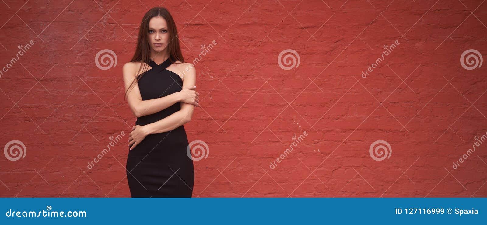 A mulher bonita elegante está vestindo o vestido preto