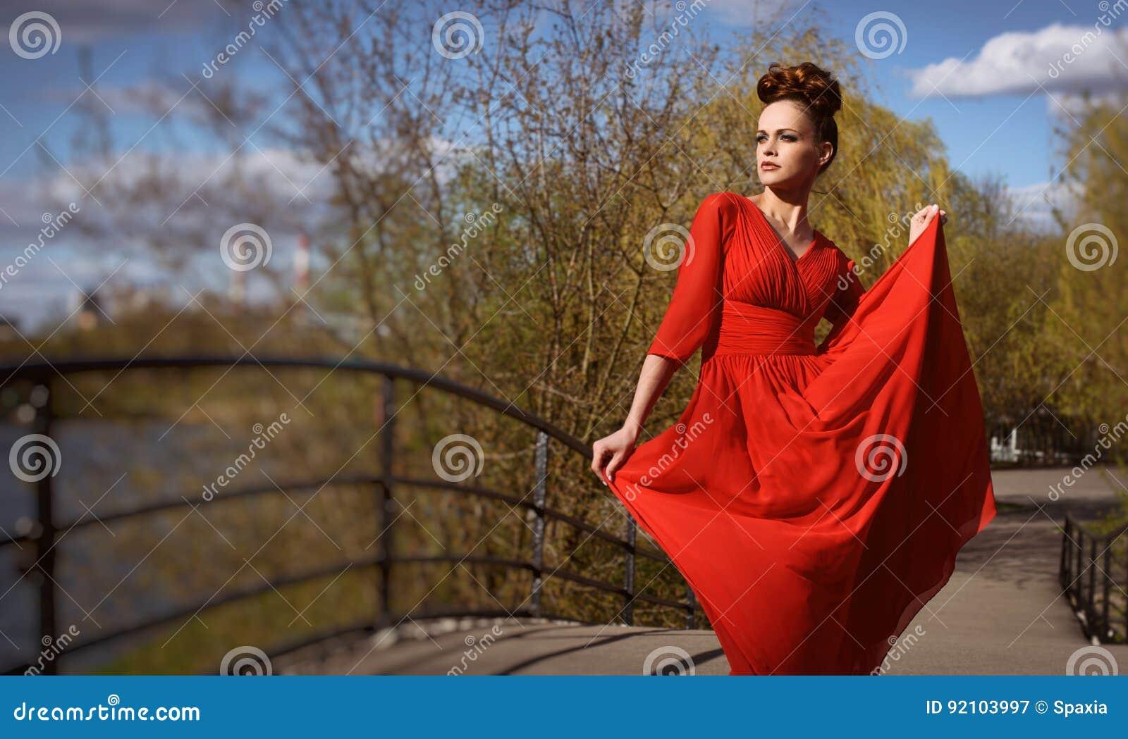 Mulher bonita elegante no vestido vermelho
