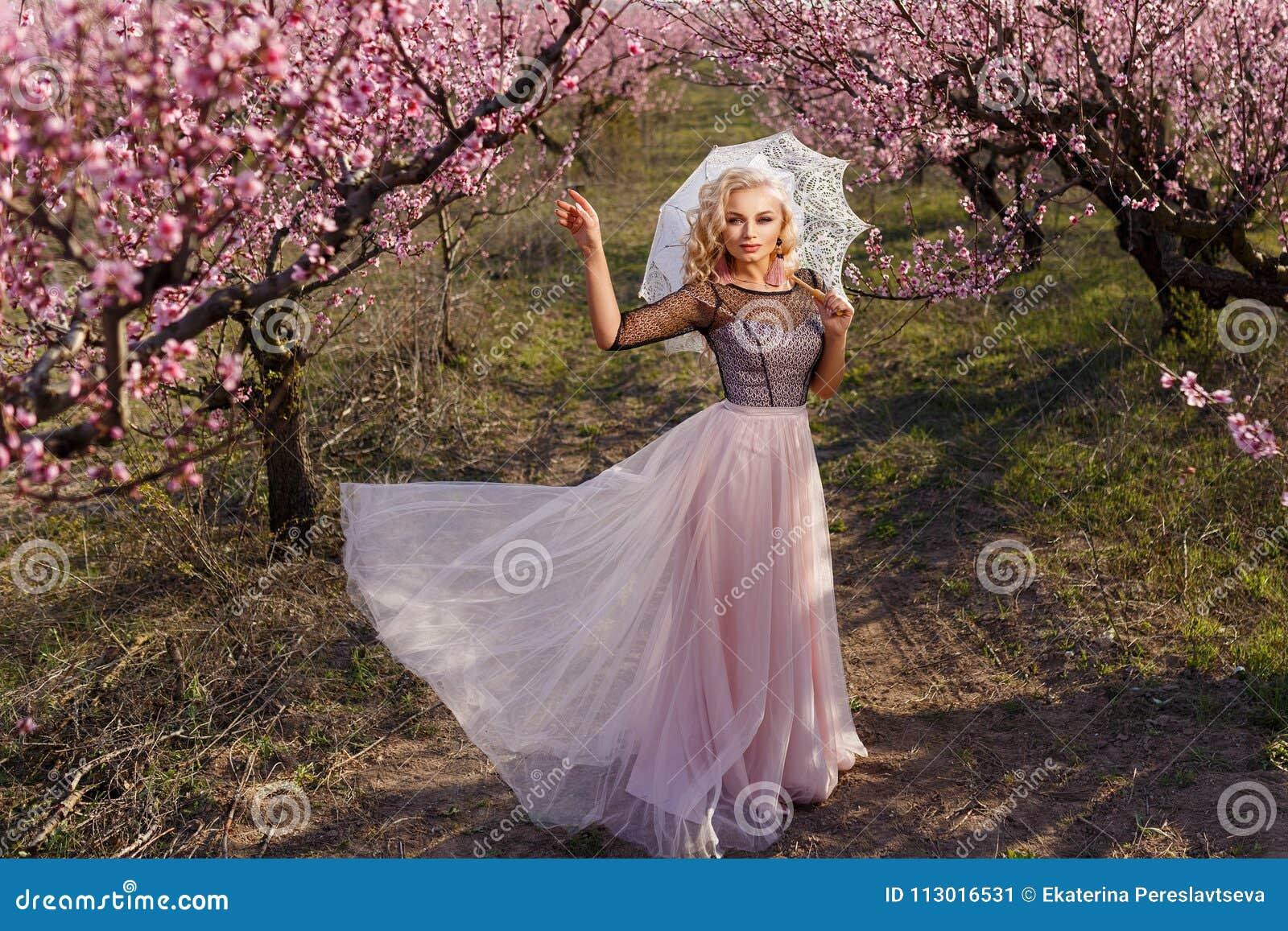 Mulher bonita em um vestido longo, no jardim de pêssegos de florescência