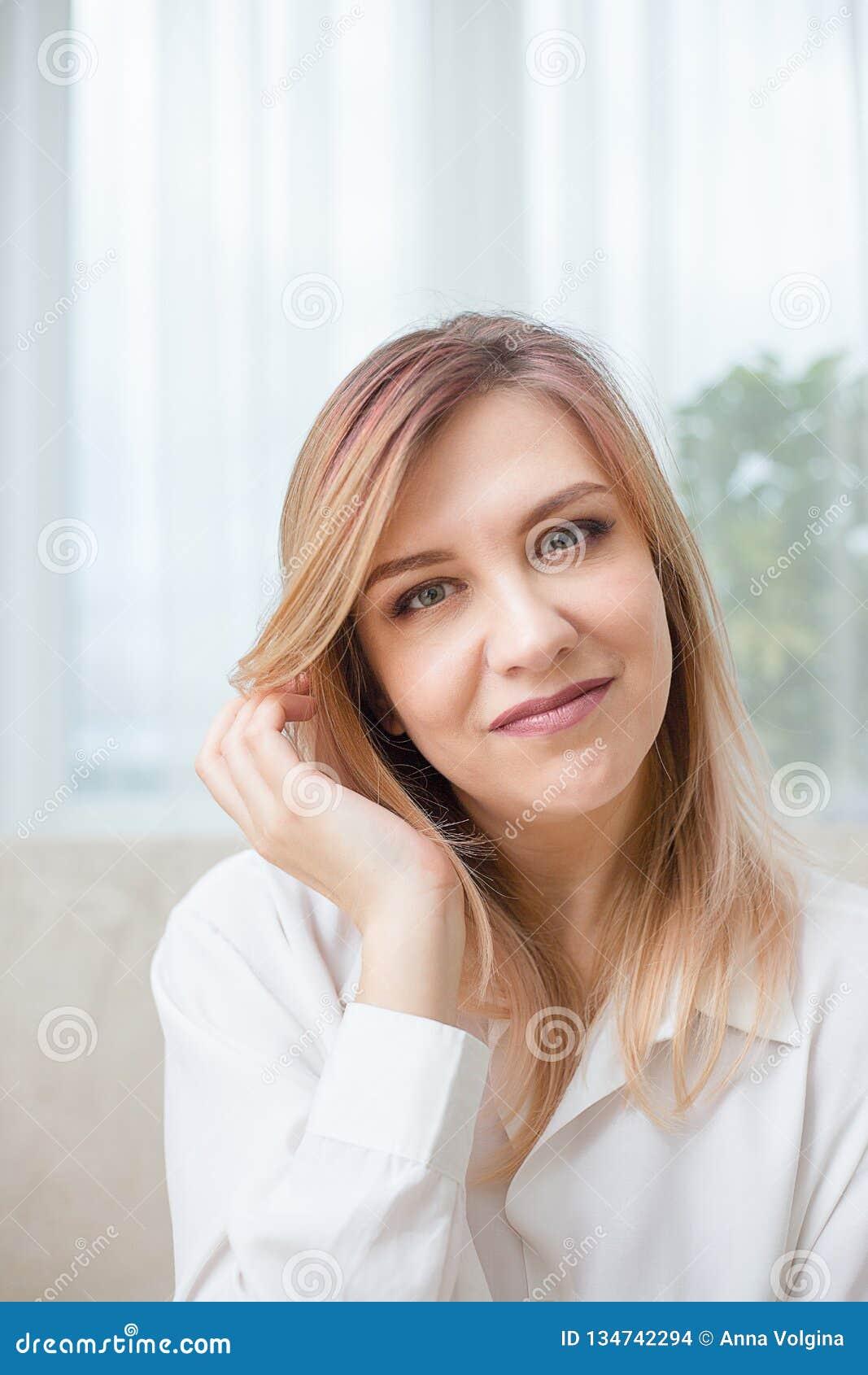 Mulher bonita em uma camisa branca em casa