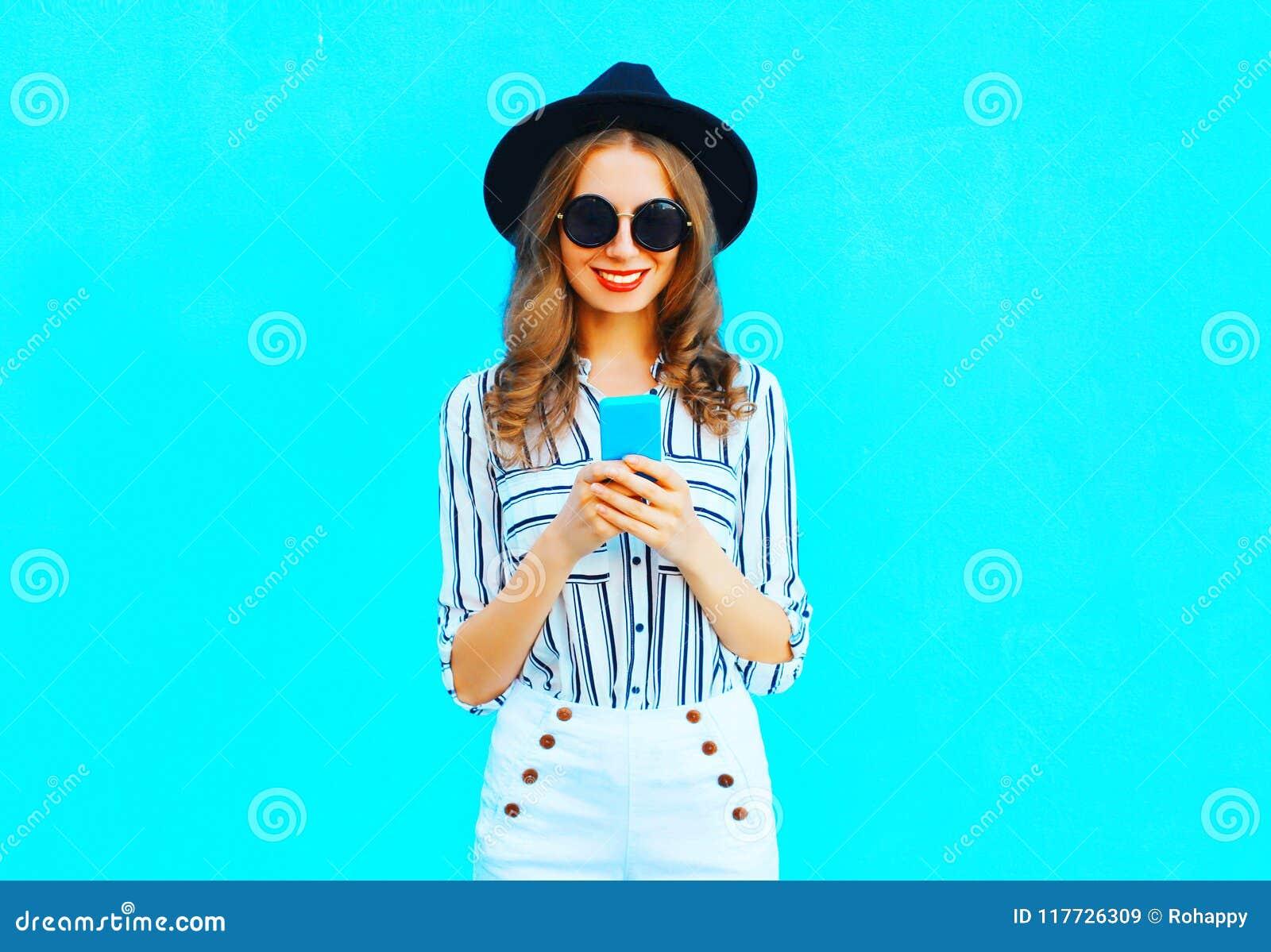 A mulher bonita está usando um smartphone que veste um chapéu negro e uma bolsa