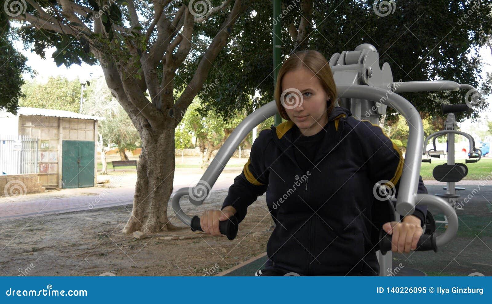 A mulher bonita faz excercises para as mãos no equipamento da rua